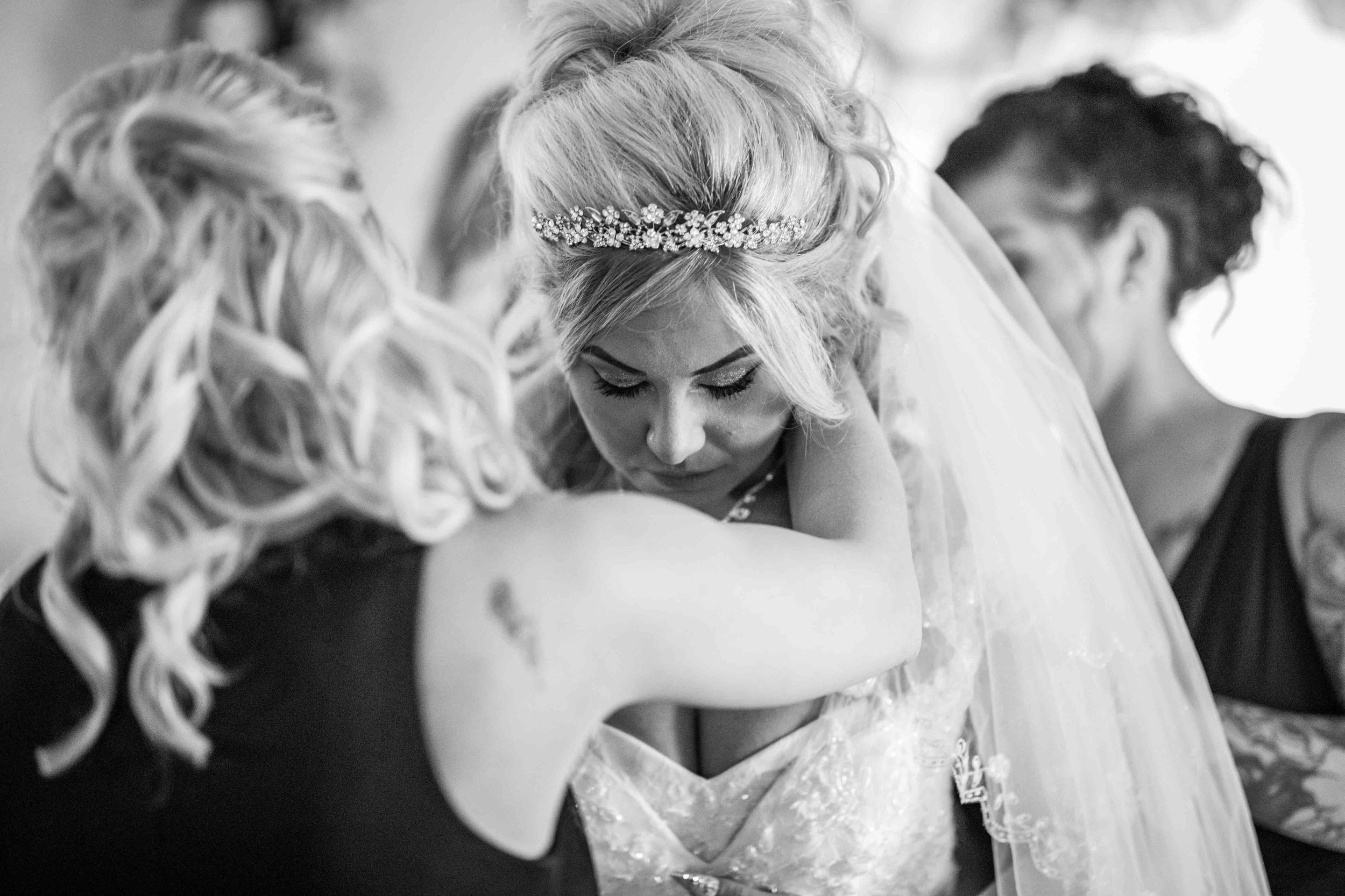 a friend puts a necklace around the bride