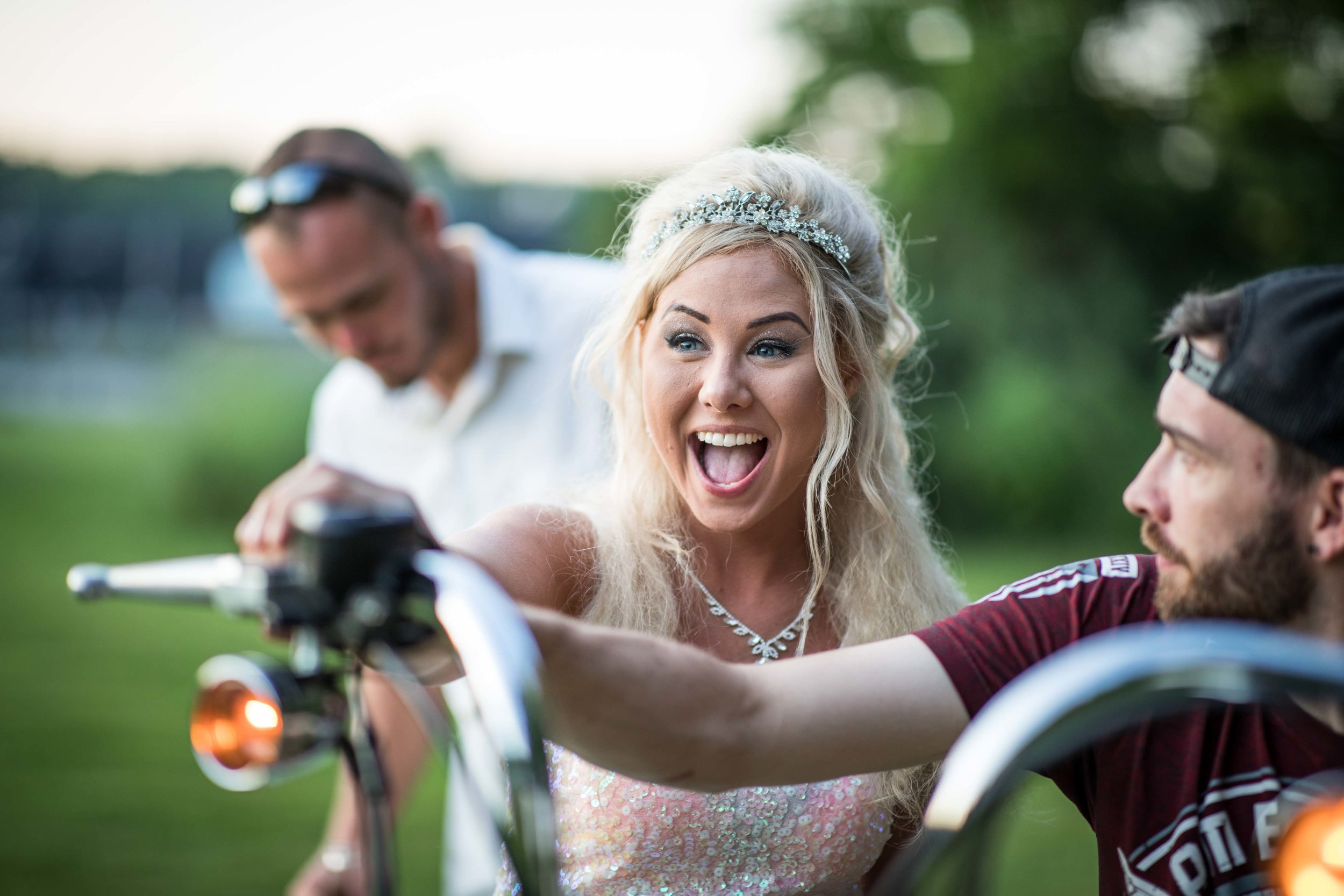 The Bride looks excited as she revs the engine of a motorcycle