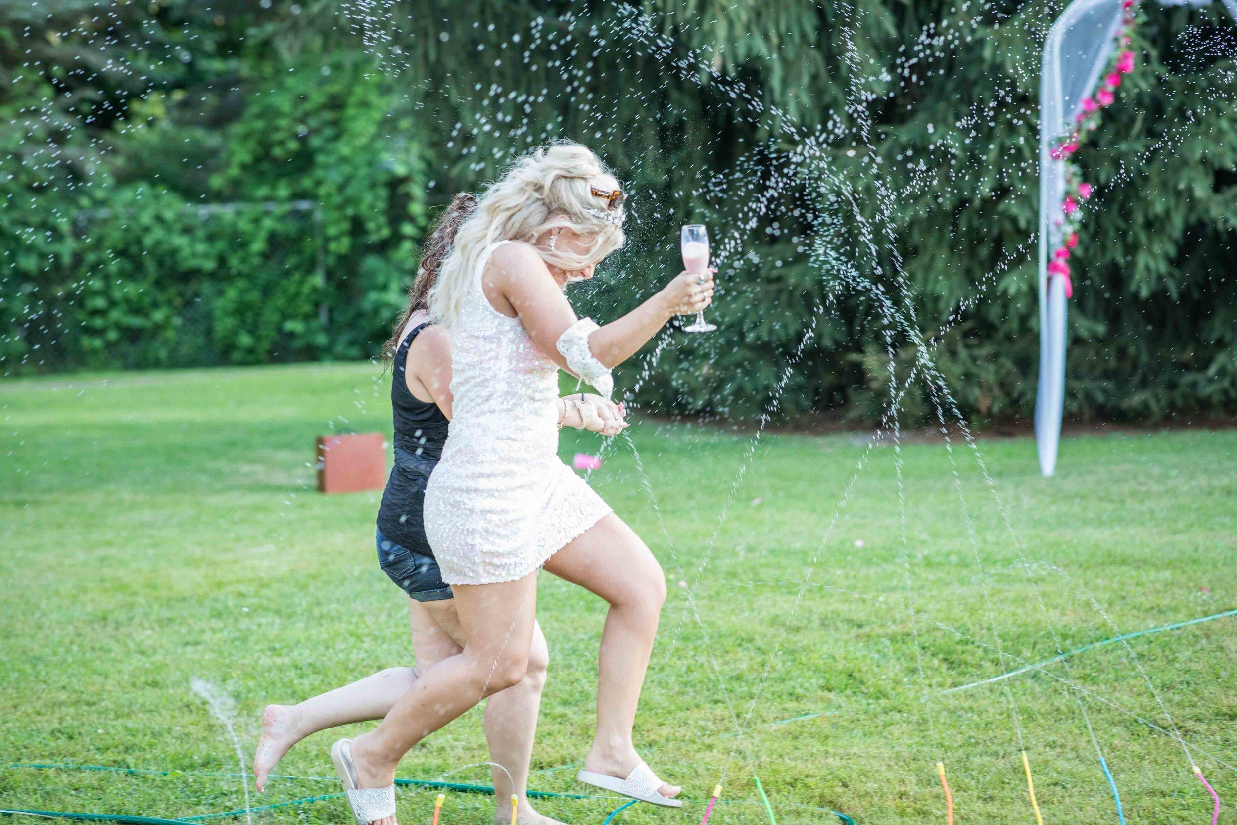 Bride running through a sprinkler system