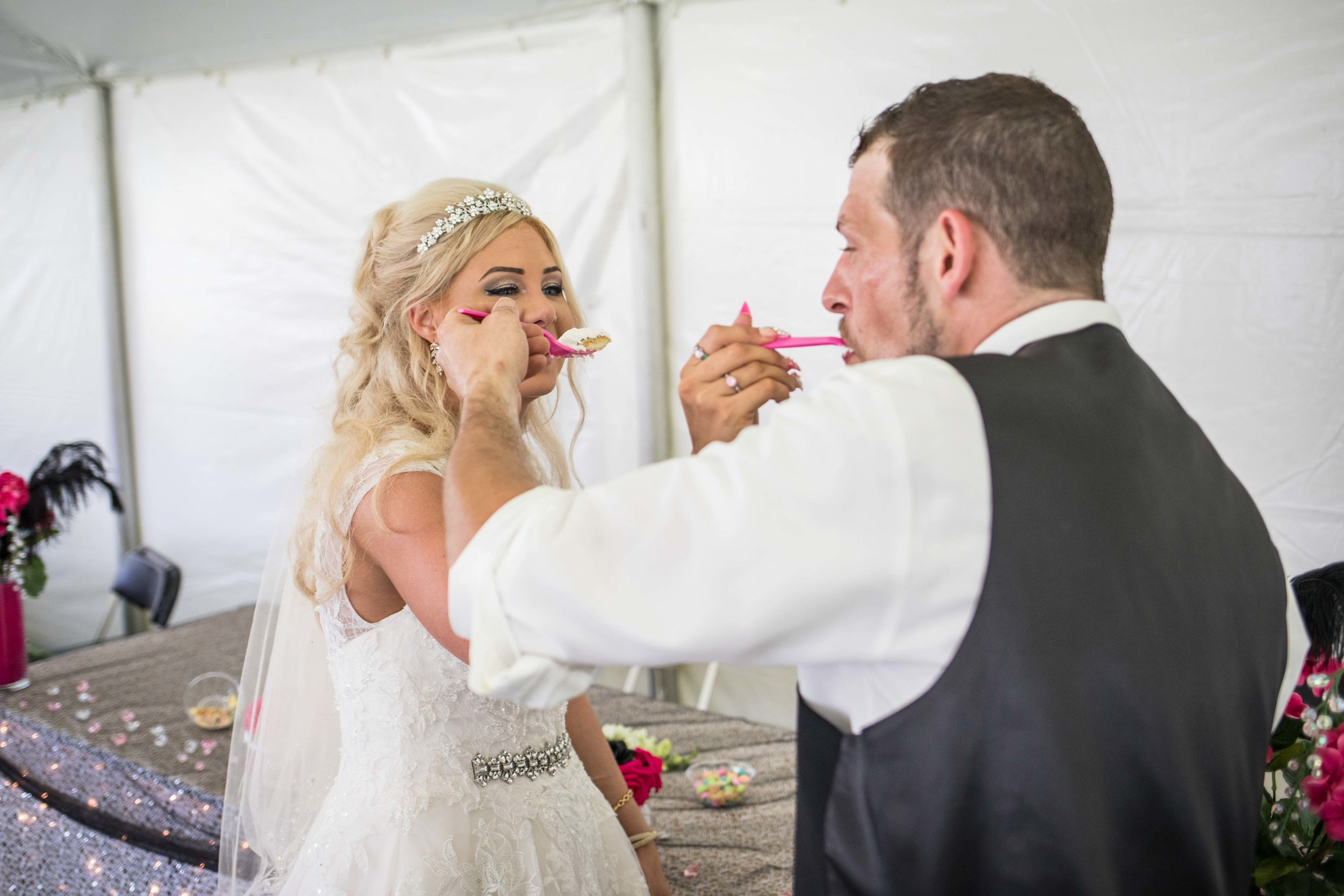husband and wife feed each other cake