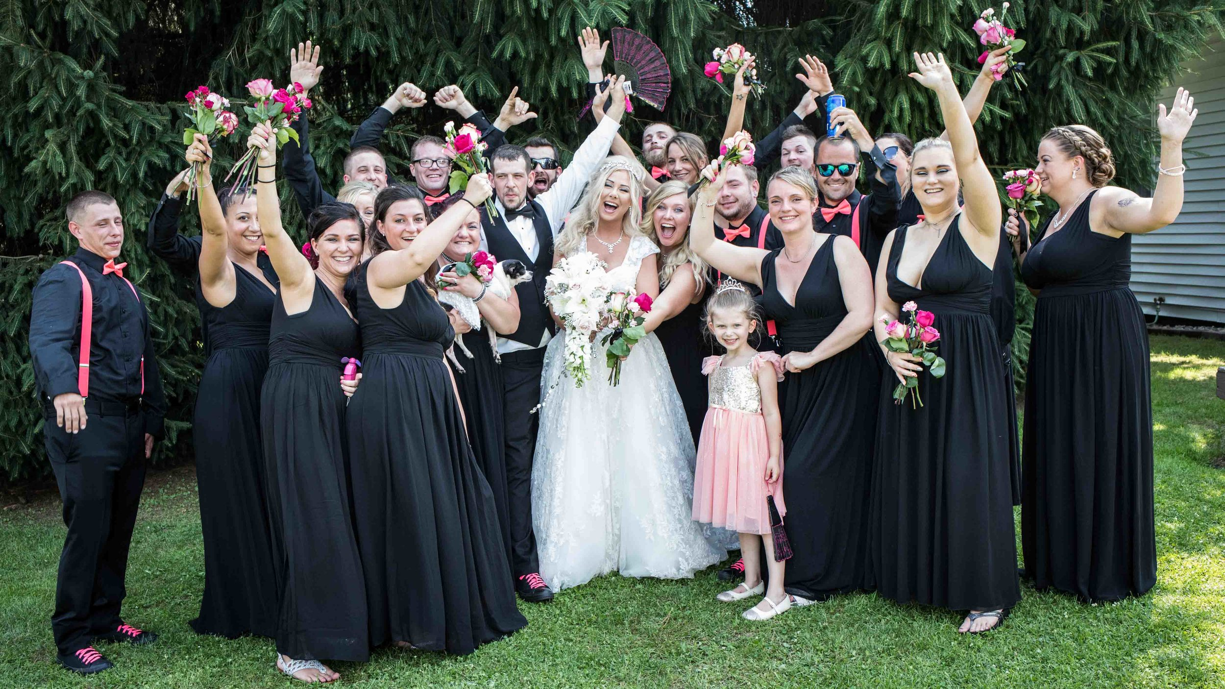 a very large wedding party celebrating with their hands in the air.  congratulating the newly weds