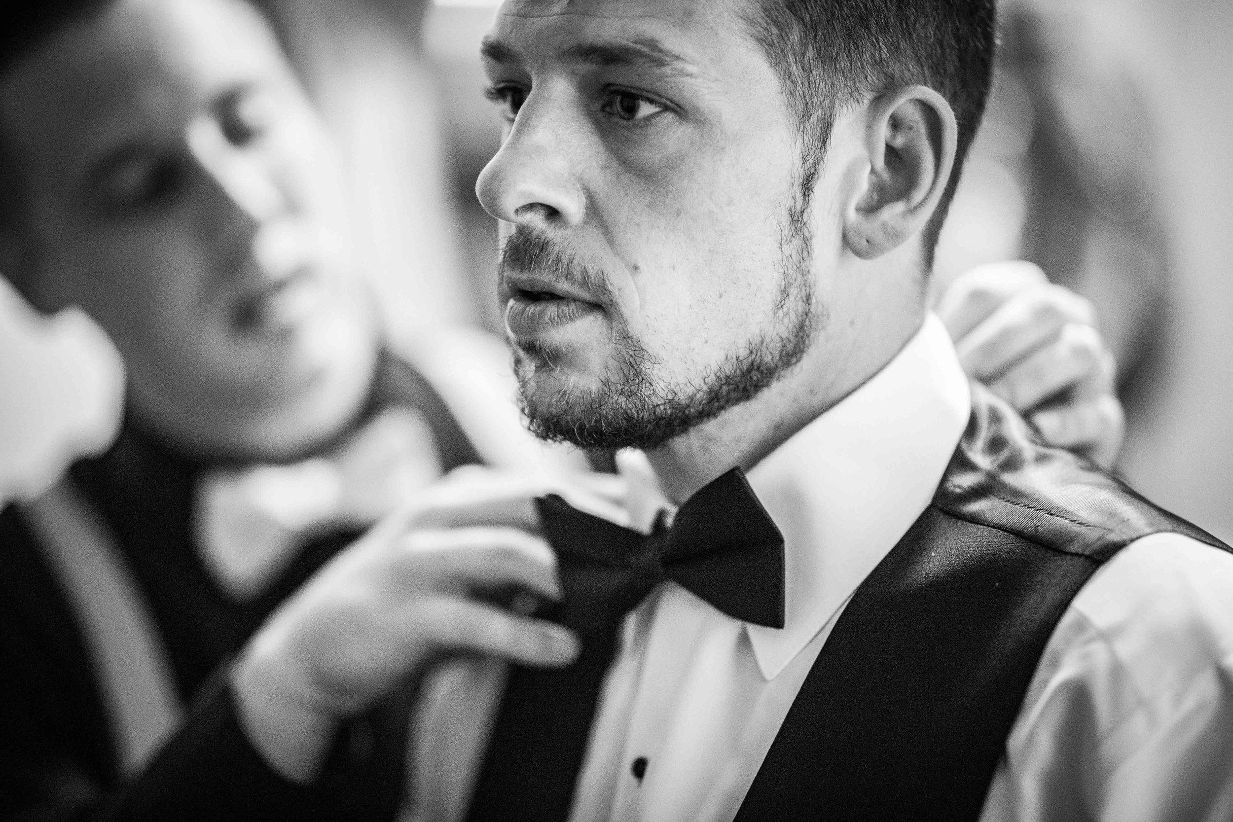 Groomsmen straitens the grooms bowtie as he looks in the mirror