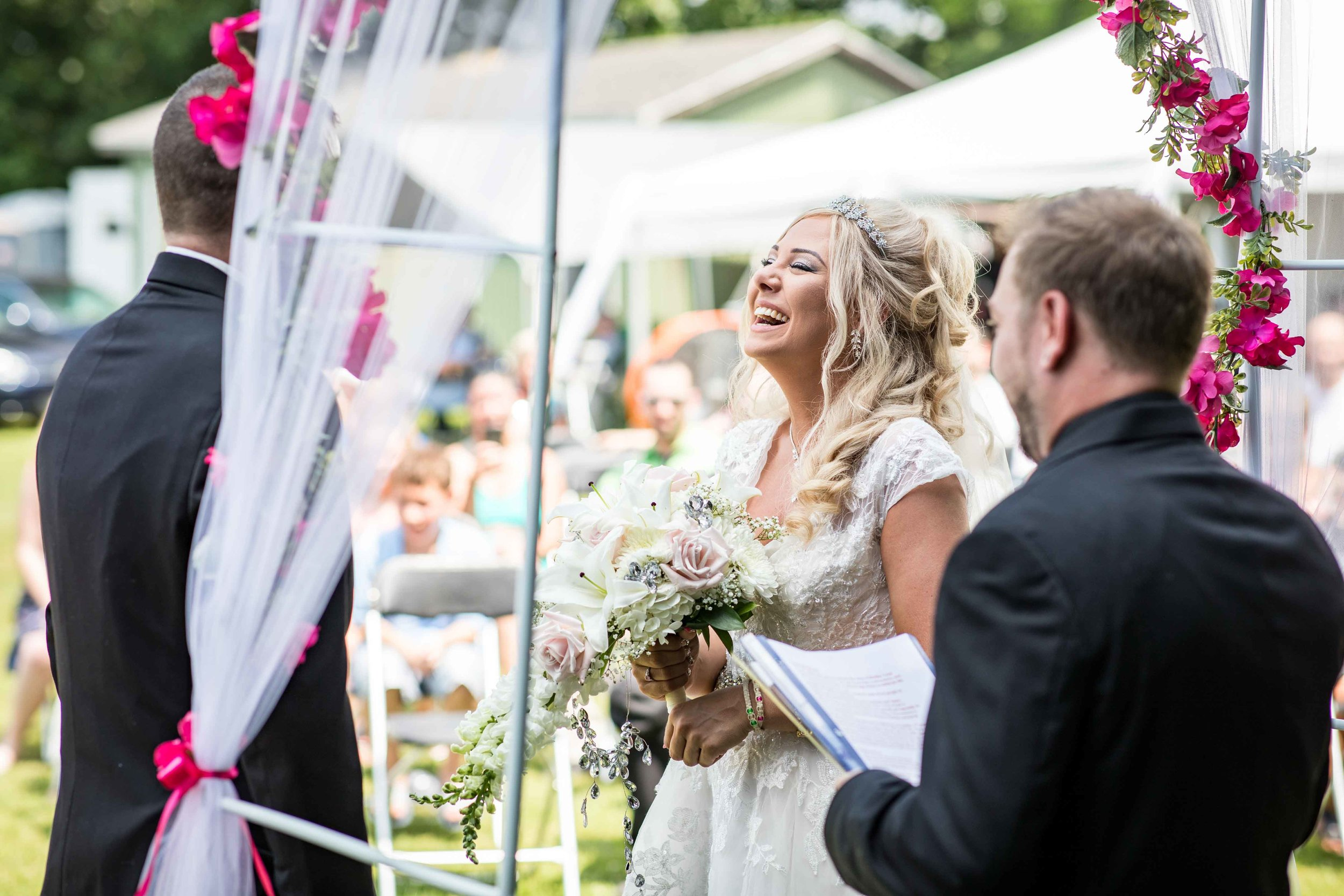 The bride laughs at a joke from the officiant