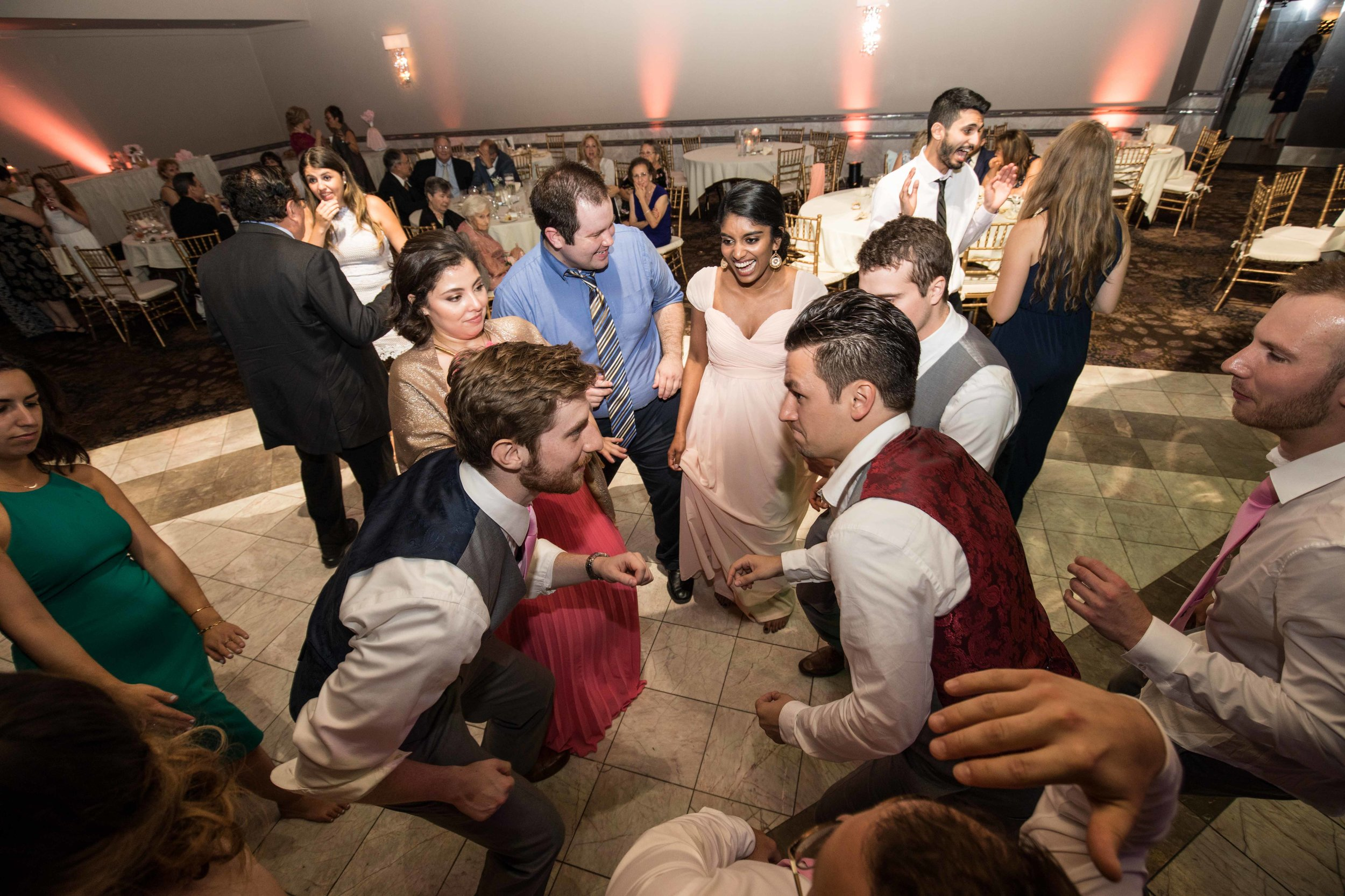 groom dancing with groomsmen and wedding guests