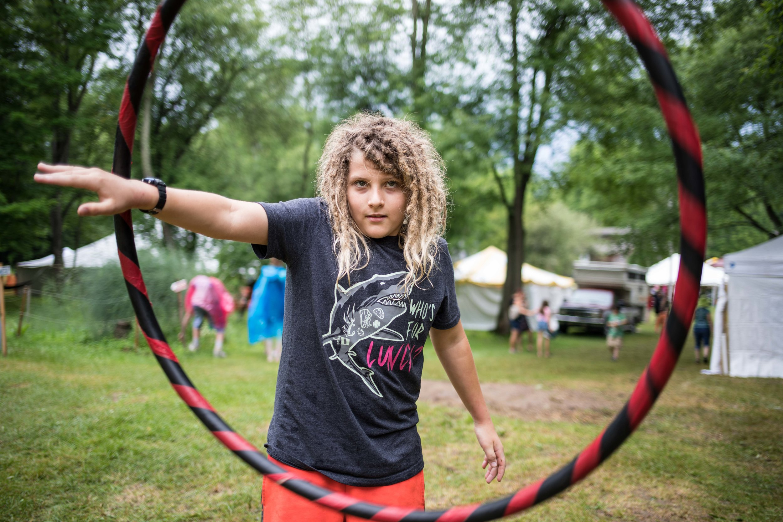 A kid facing the camera spinning a hula hoop in his arms