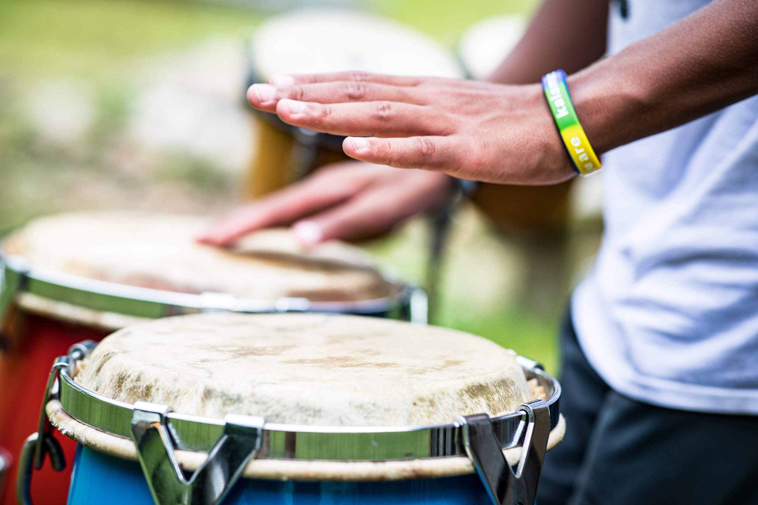 A childs hands playing bongo drums
