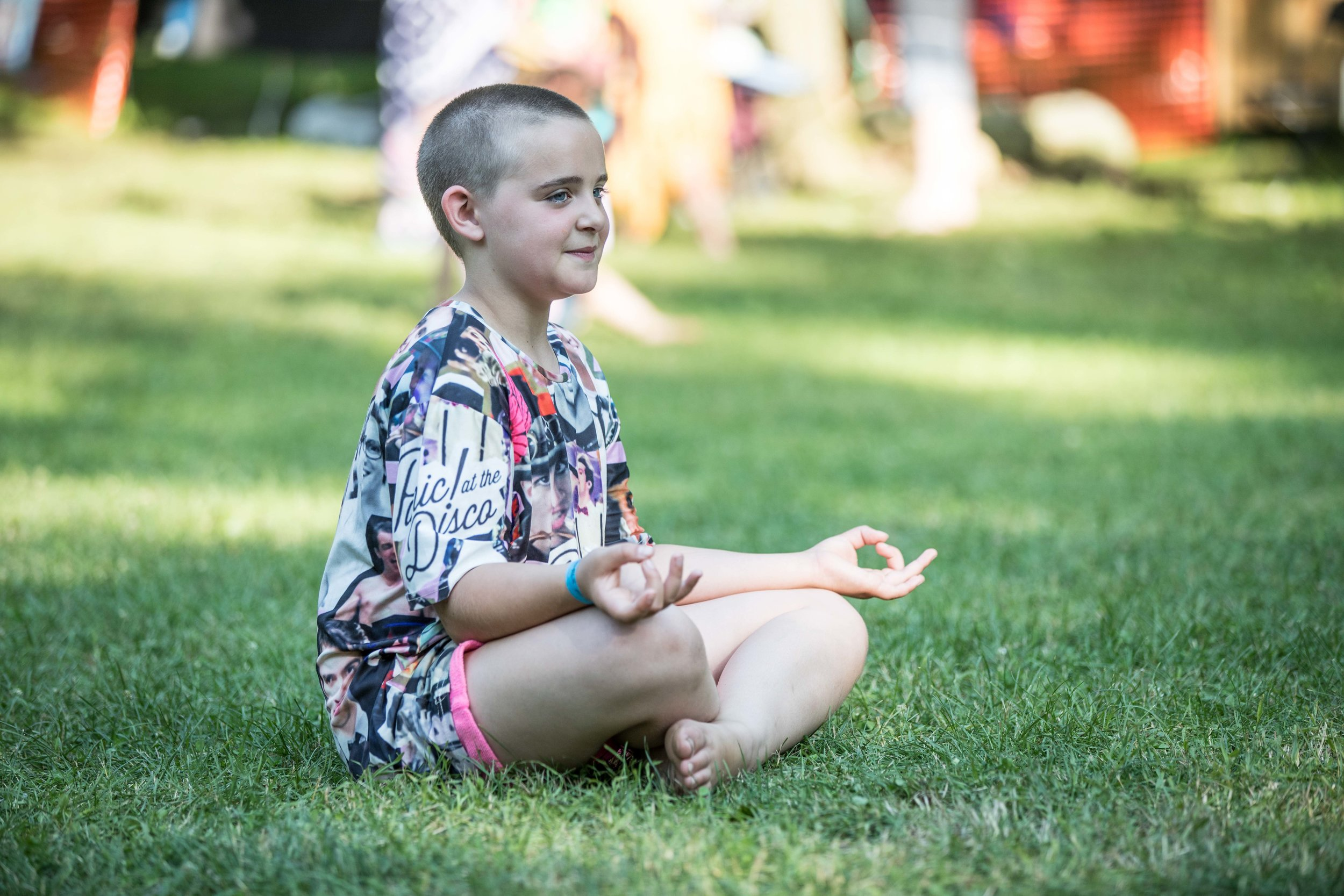 a child meditating in the grass