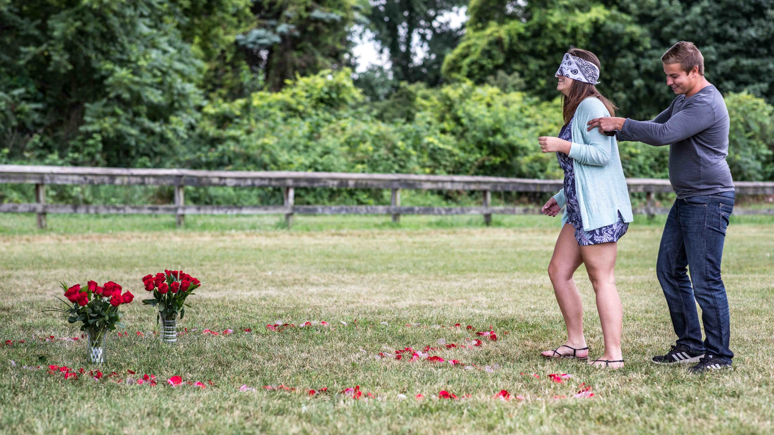 The boyfriend positions his blindfolded girlfriend in place at the top of a heart made of flower pedals