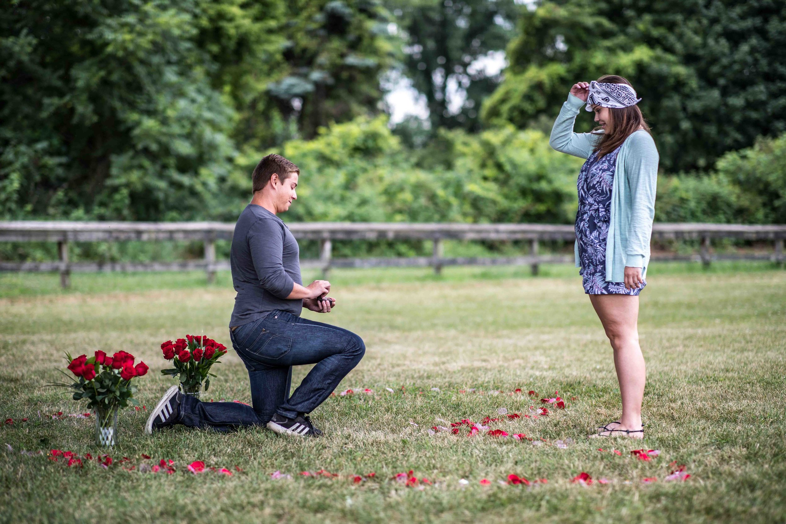 Girlfriend removes her blindfold to find her boyfriend proposing to her with flowers in the shape of a heart around them