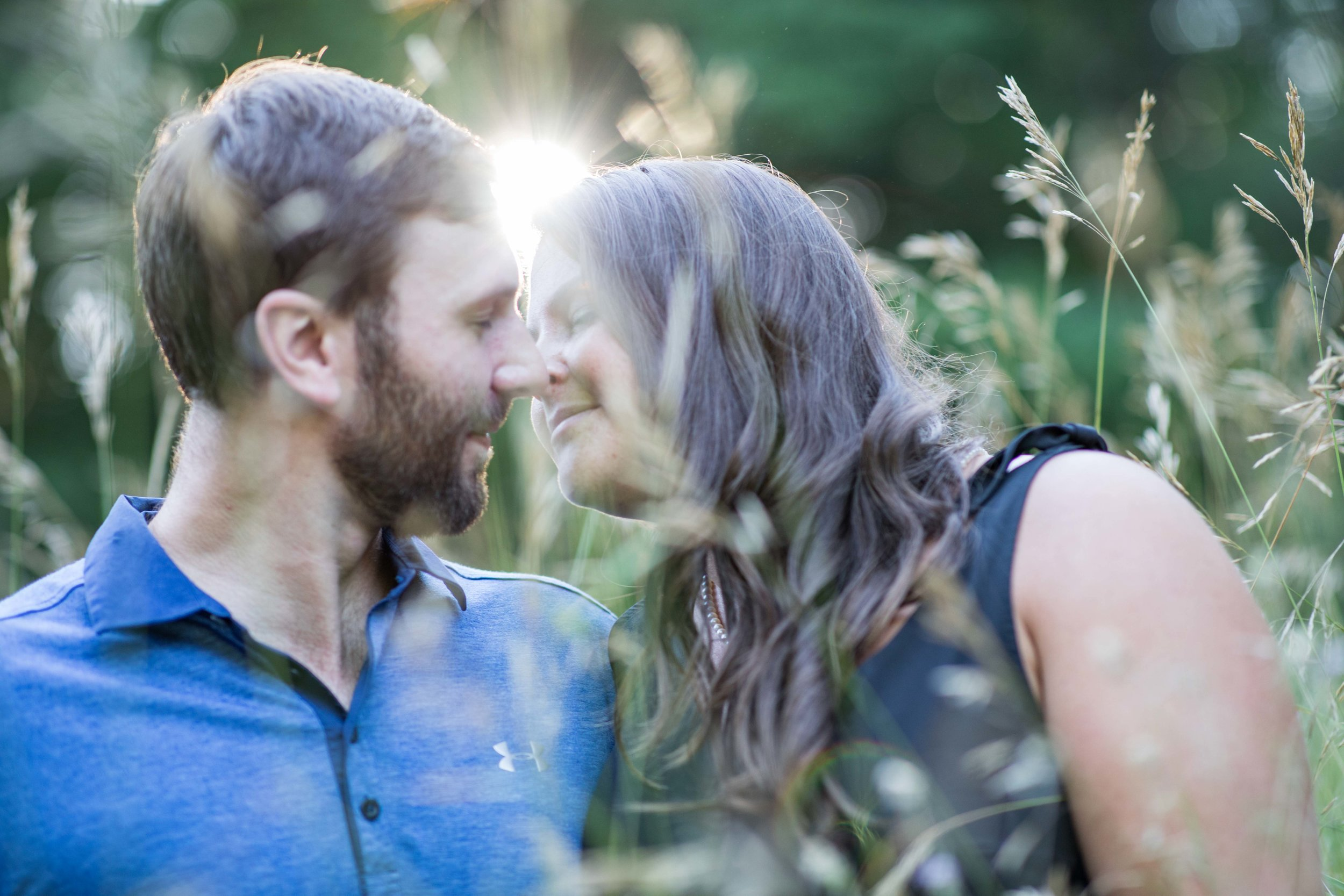man and woman kissing in tall field grass behind a setting sun