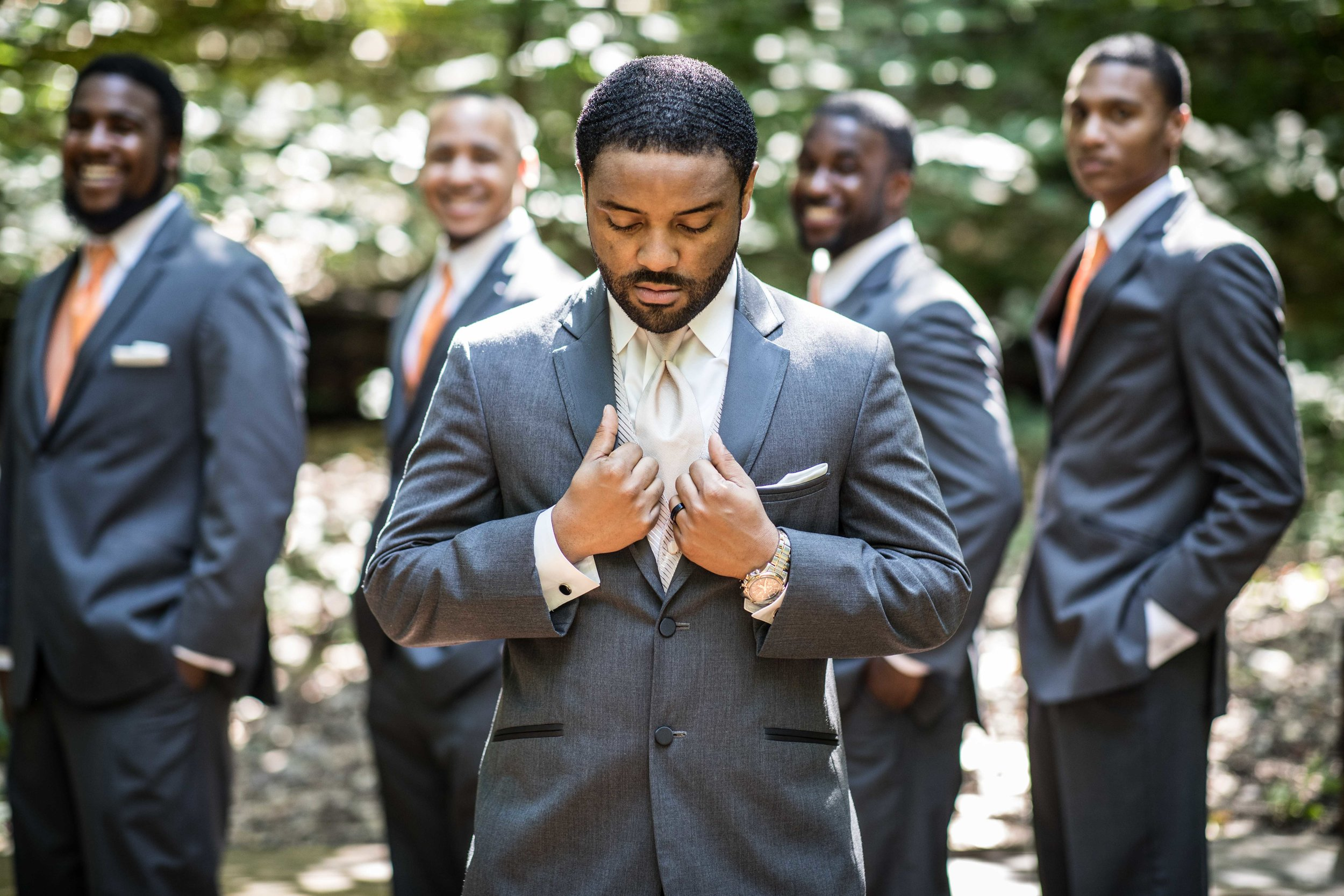 The groom straightening his suit with groomsmen lined up behind him