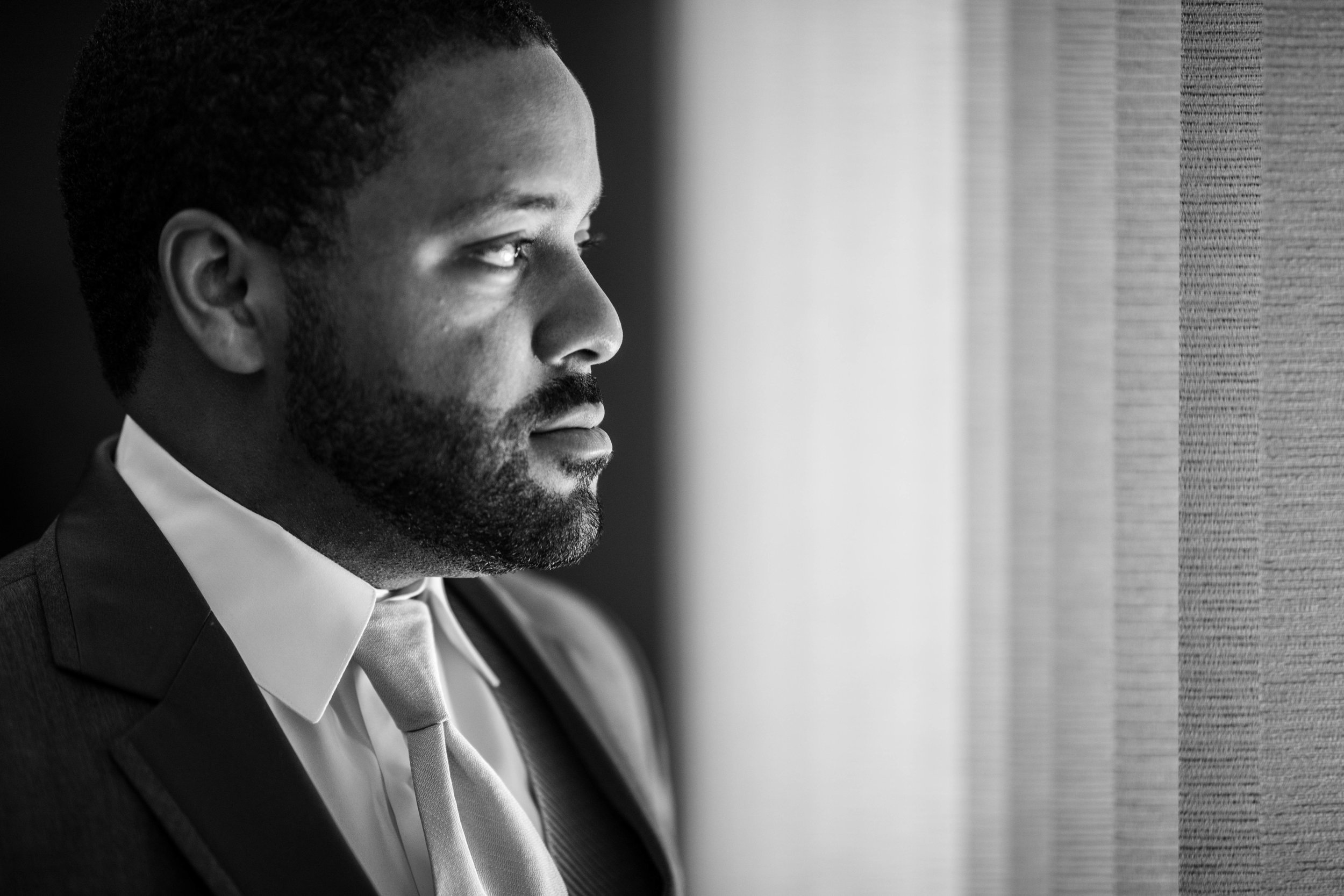 dramatic Black and White photo of the groom looking out of a window