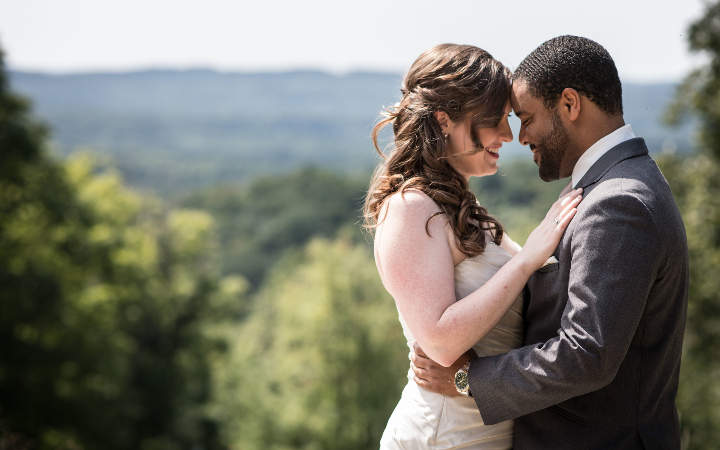 bride and groom hold each other with a mountainous backdrop