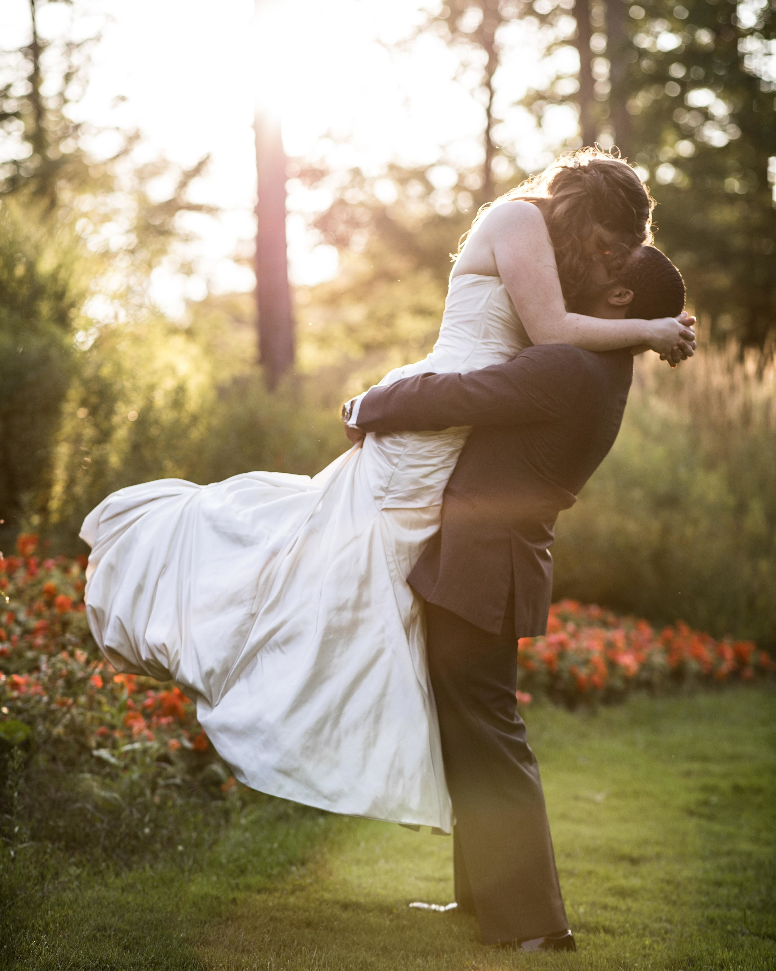 The groom lifts the bride up in the air as she kisses him with sunset and flower landscape behind them