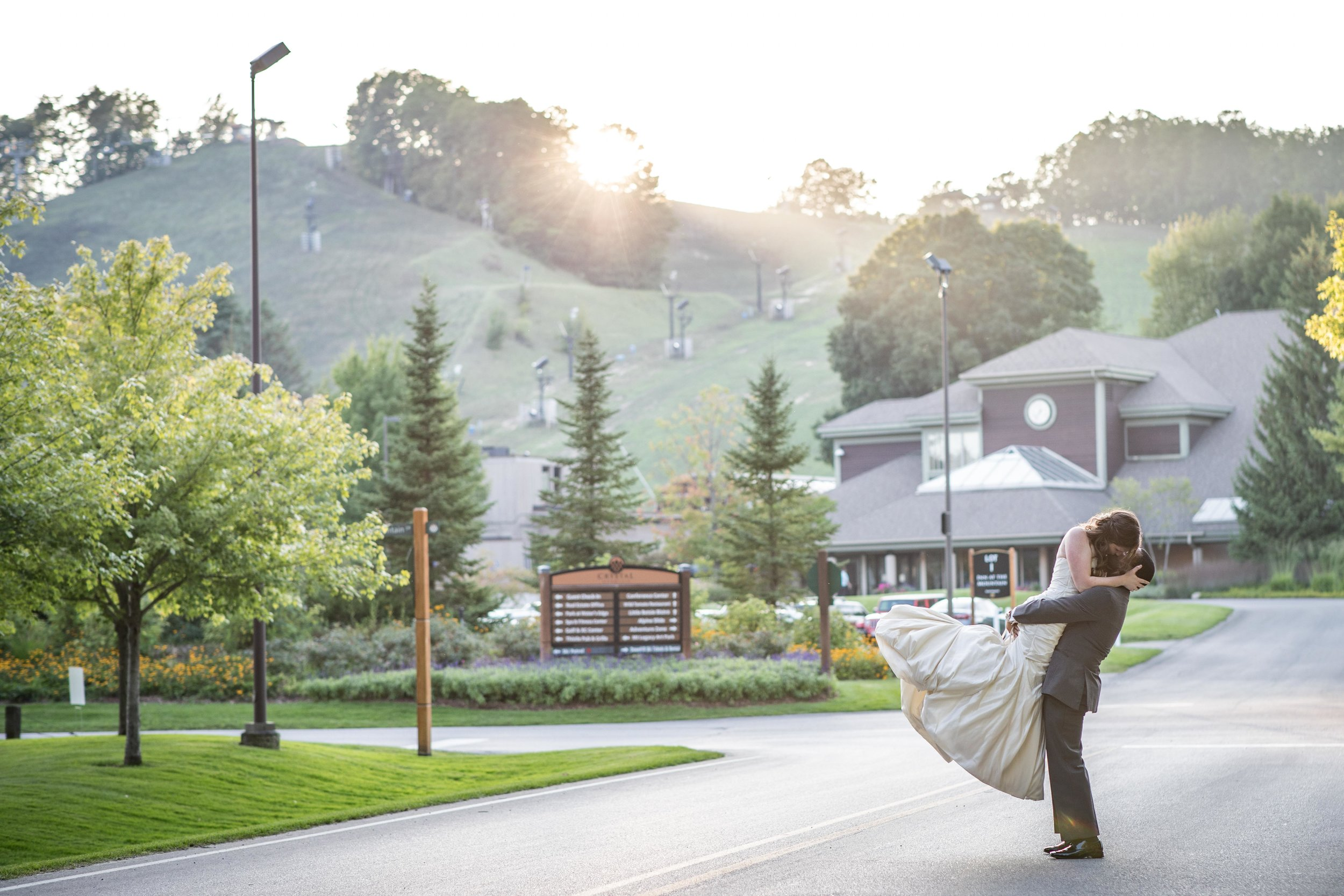 dramatic landscape photo of crystal mountain in Michigan with groom lifting bride as she kisses him during sunset over the mountains
