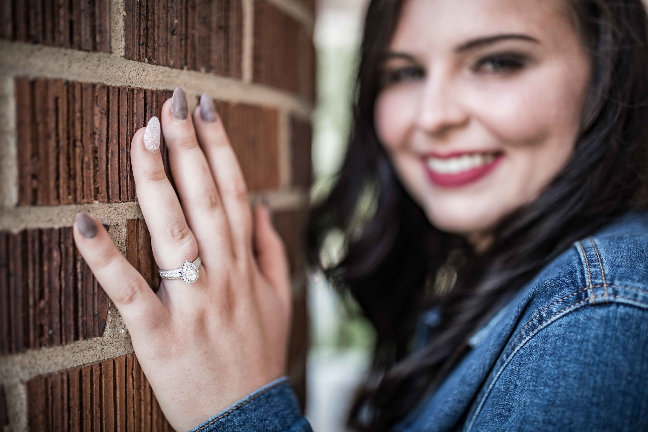 she shows off her engagement ring against a brick pillar