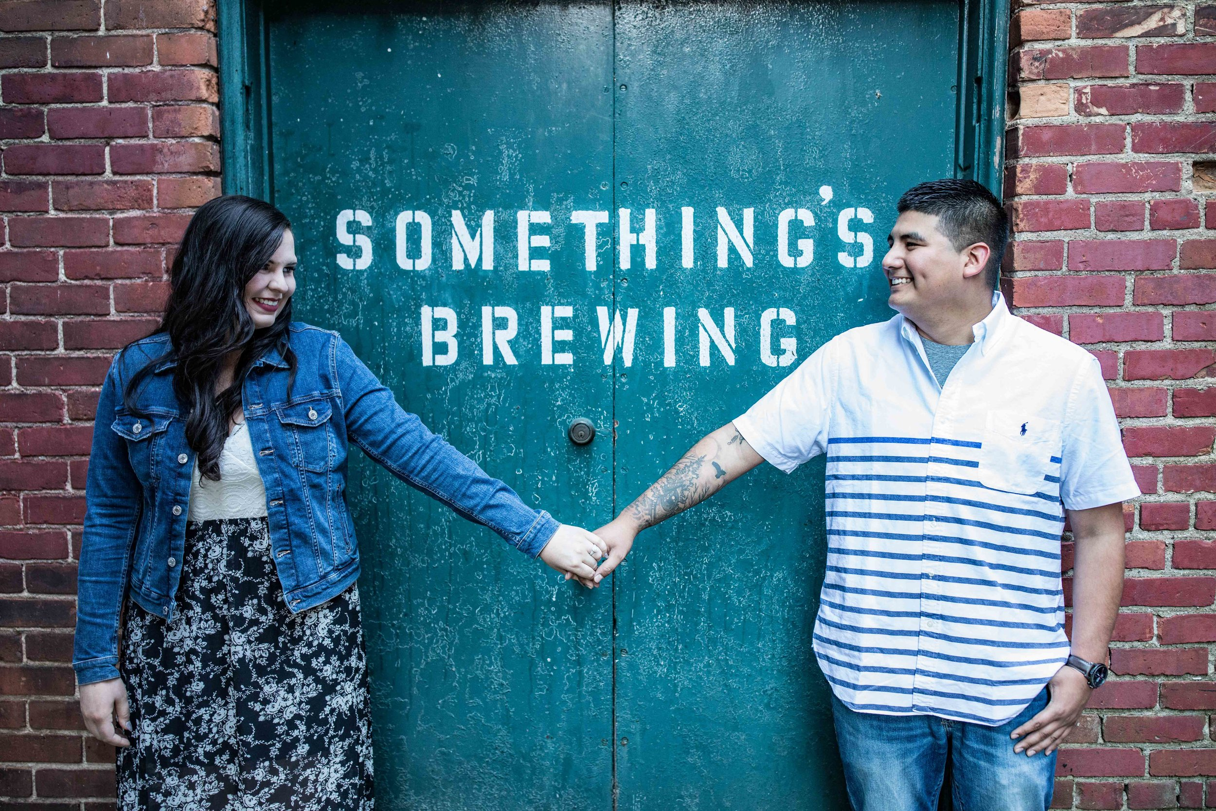 Man and woman hold hands in front of a green double door that says Something's Brewing