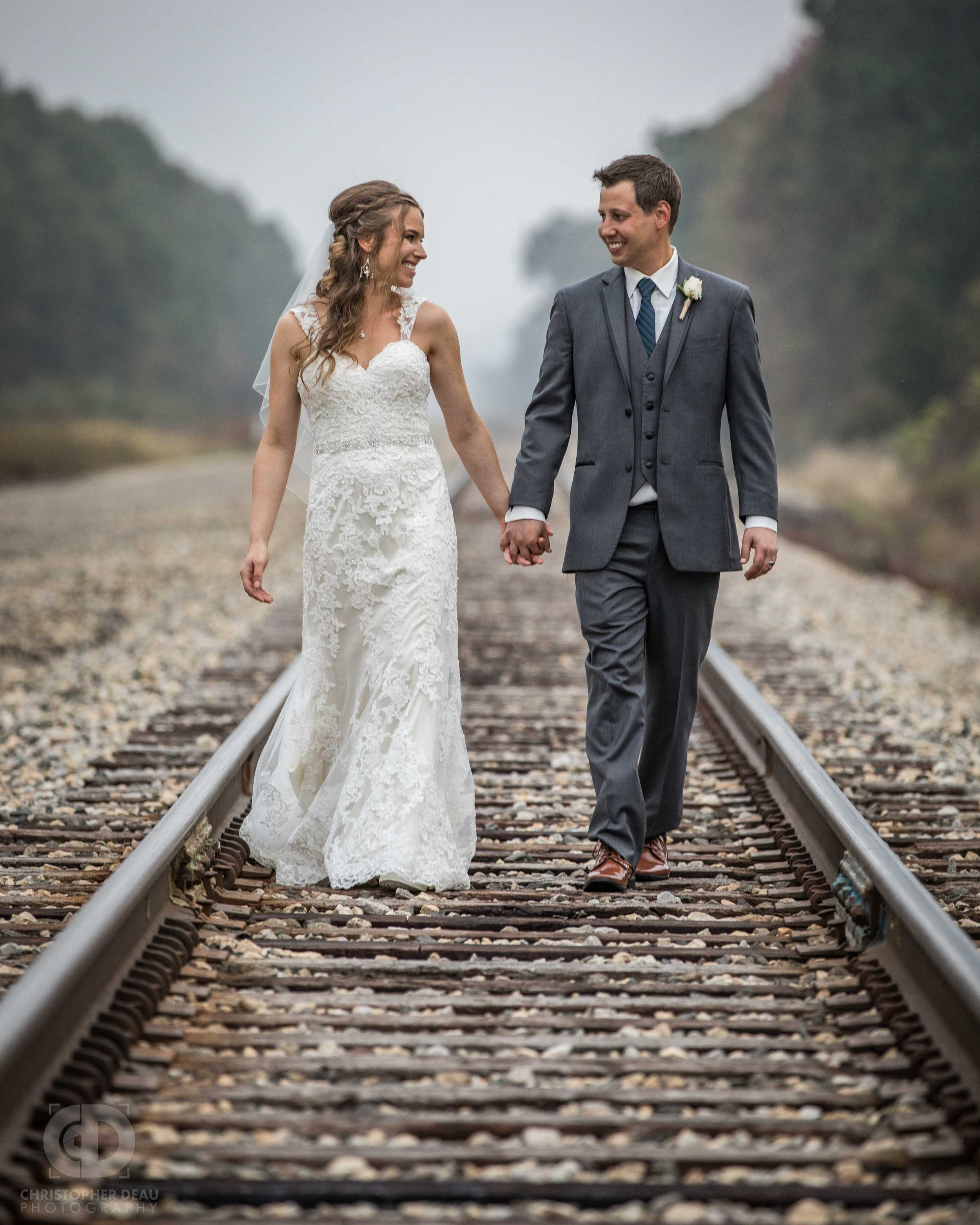 bride and groom walking down railroad tracks