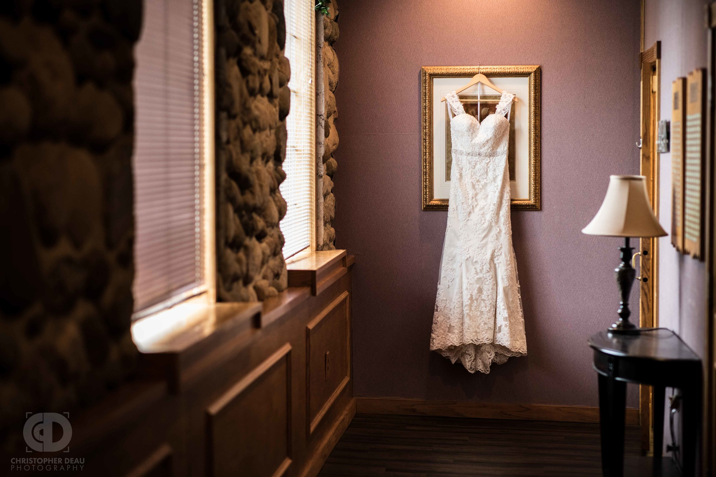 The brides white dress hanging at the end of a hallway