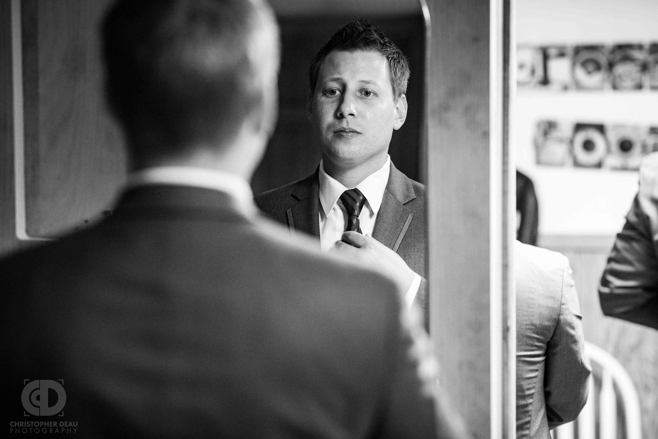 Groom straightening tie in the mirror