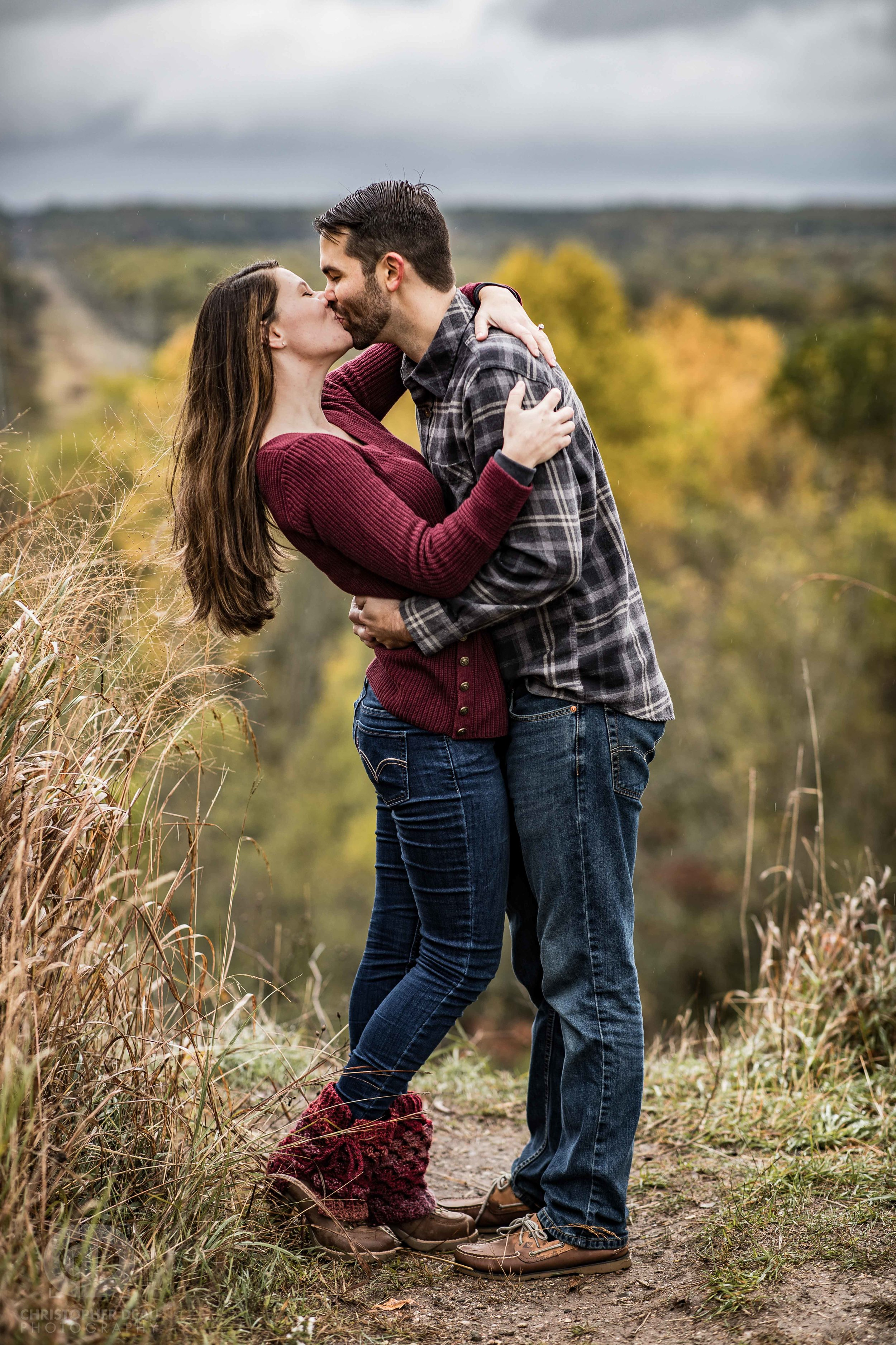 man kisses woman in front of bluff overlook at the kalamazoo nature center in southwest michigan