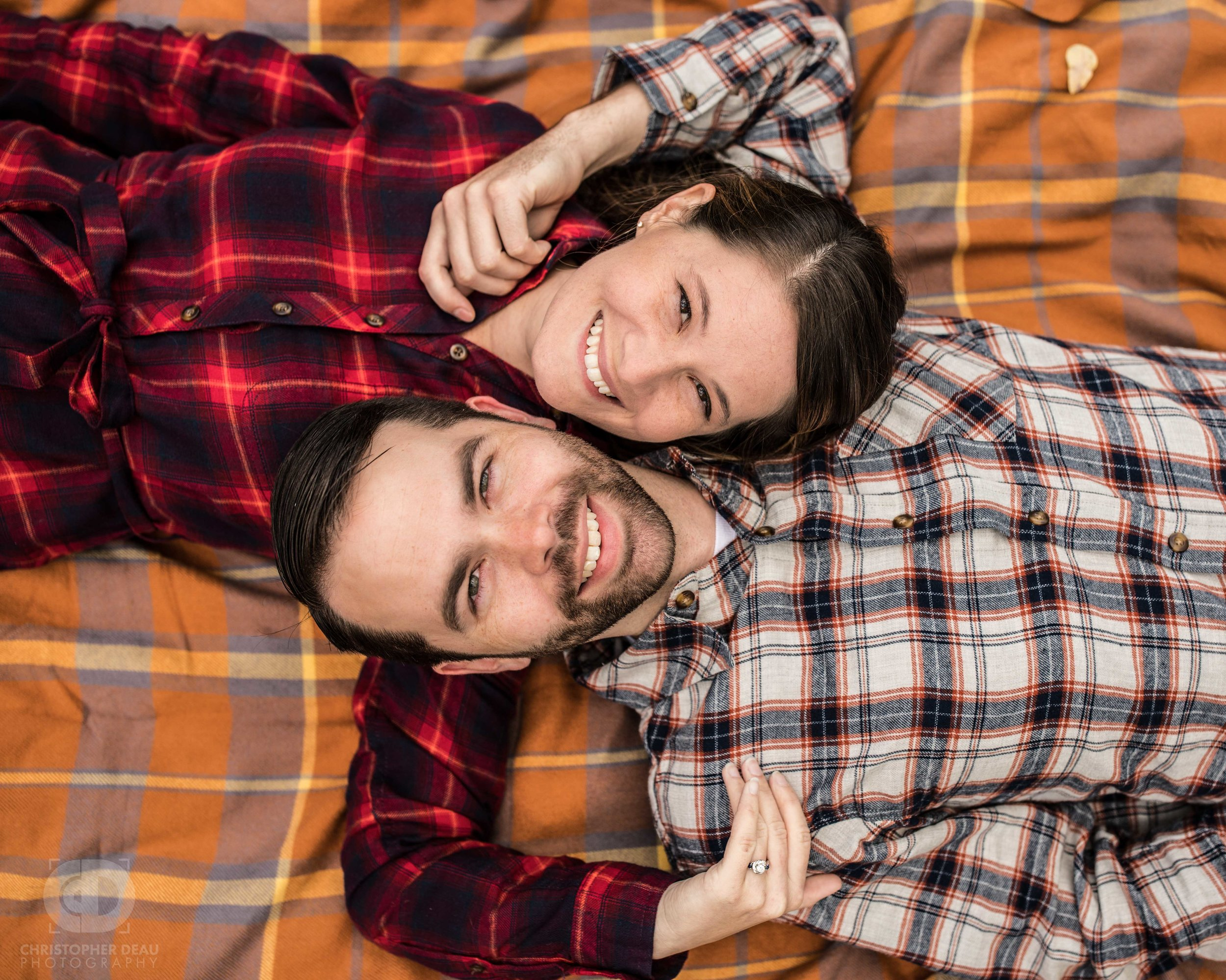 engaged couple laying down on fall blanket, looking up at camera
