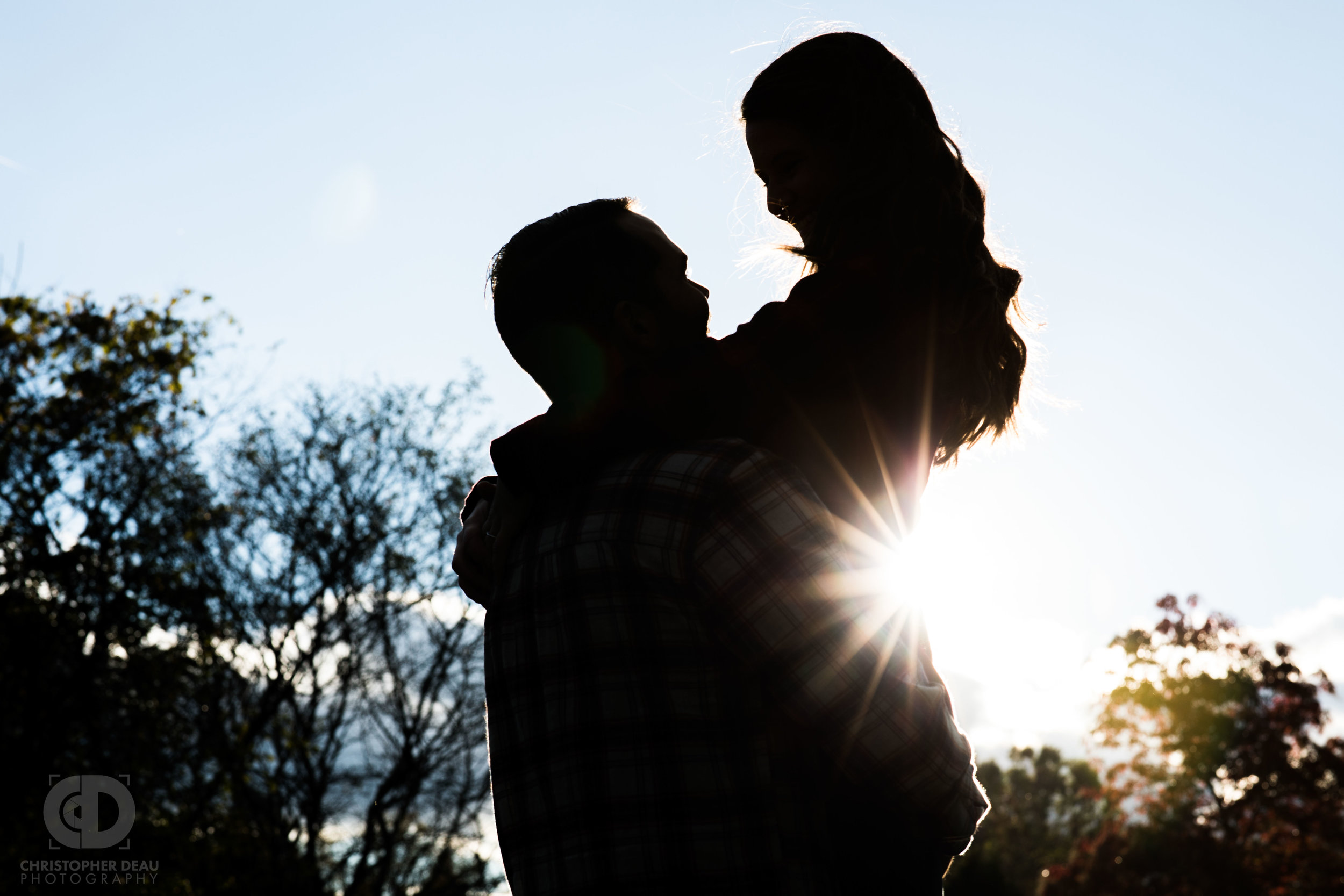 Silhouette of man lifting woman with the sun glaring behind
