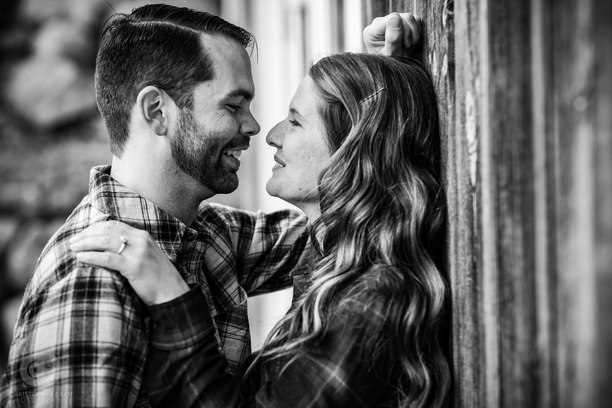 black and white image of engagement photos with man and woman against a rustic wood barn in Southwest Michigan