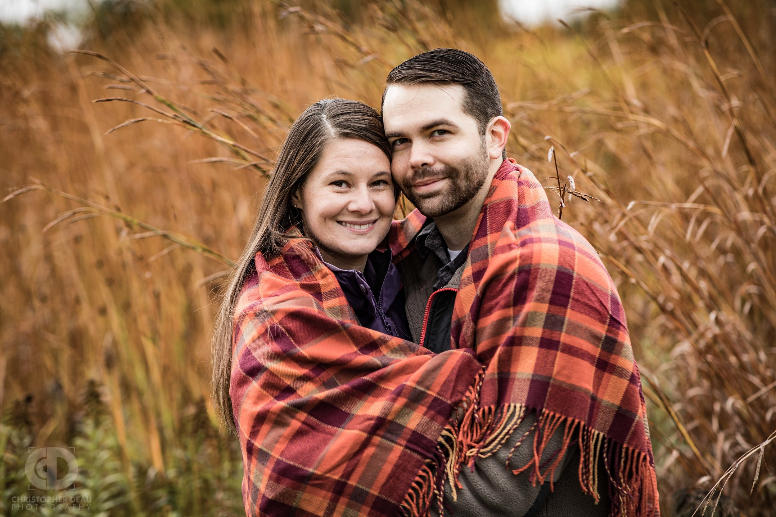 couple wrapped in blanket during cold fall day in a tall grass prairie in southwest Michigan