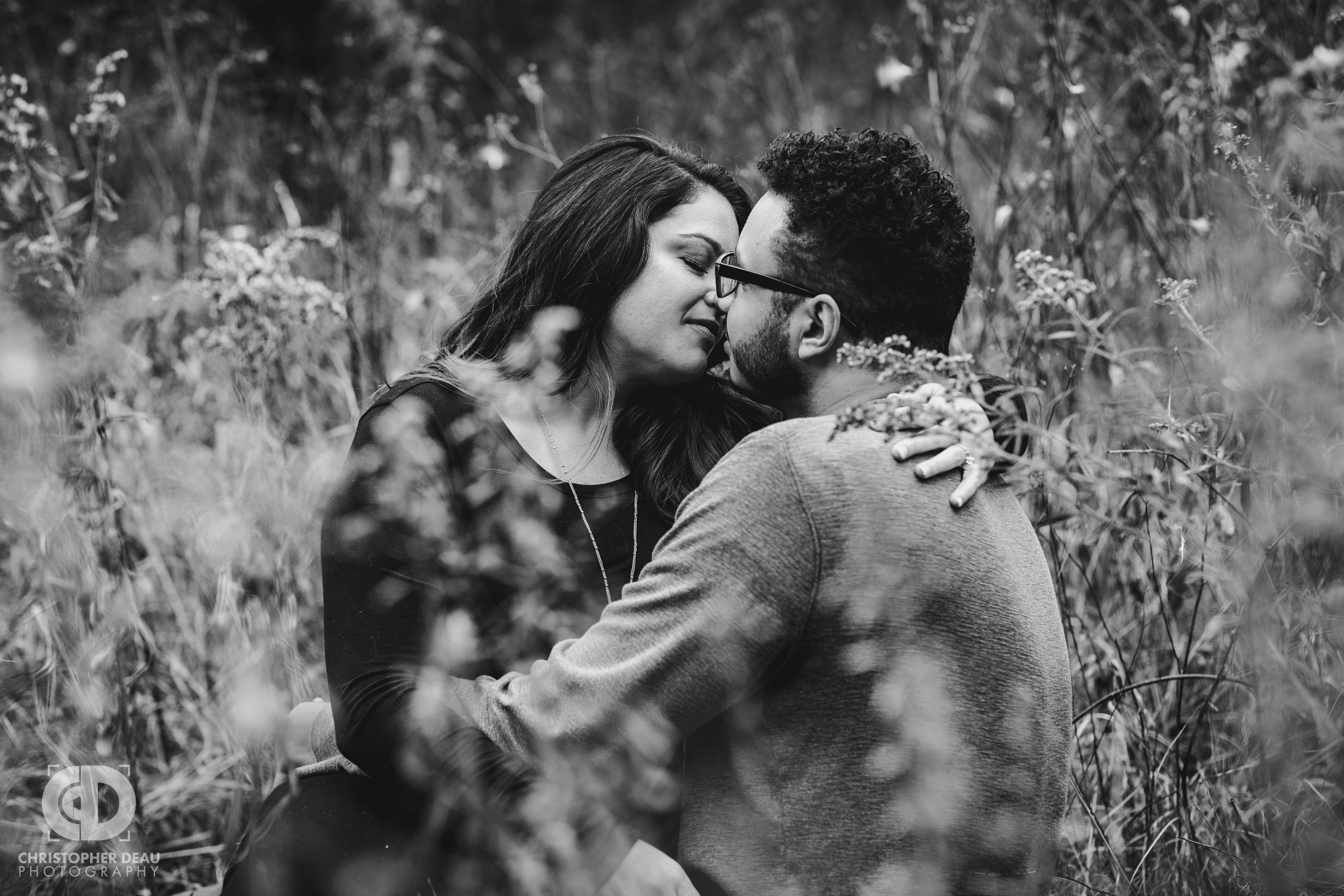 black and white image of man and woman sitting in a tall grass prairie for engagement photos in Kalamazoo Michigan
