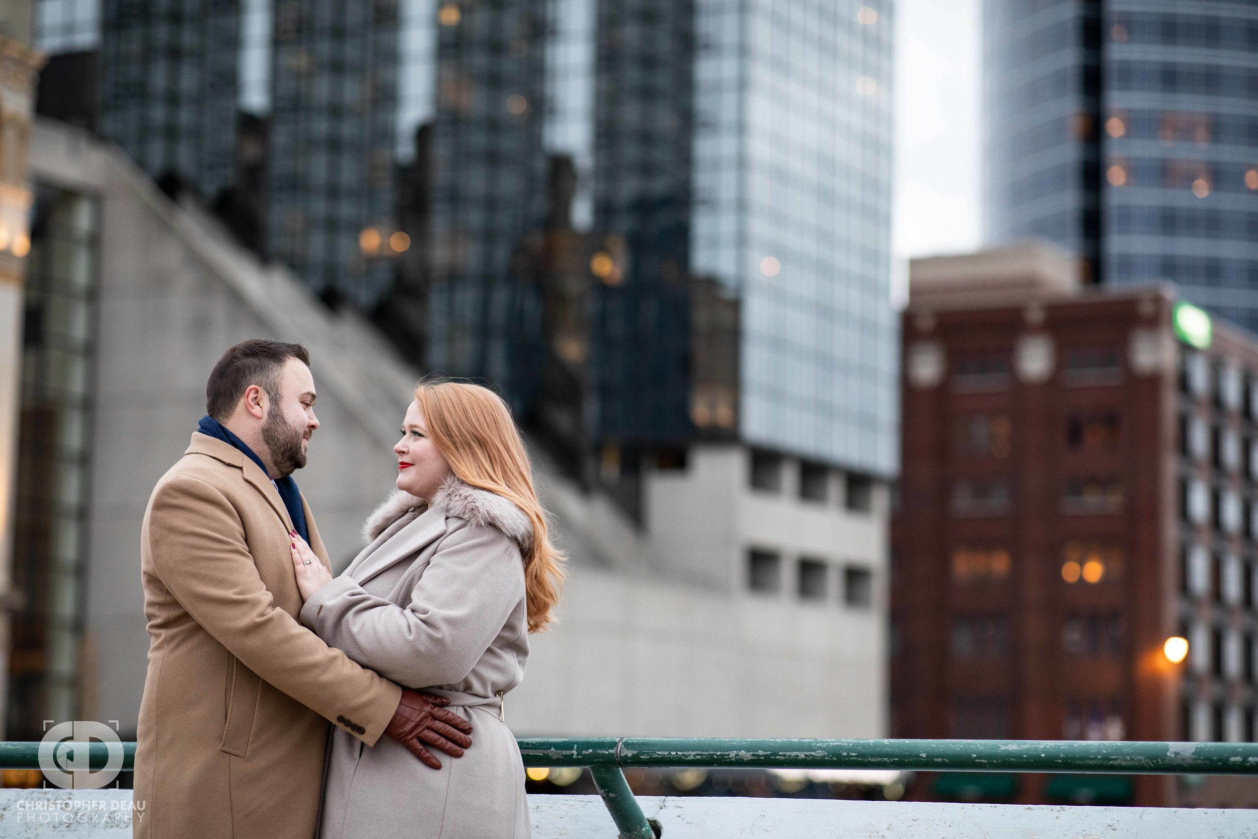 Engagement session photos on a bridge over the Grand River with Grand Rapids skyline in background