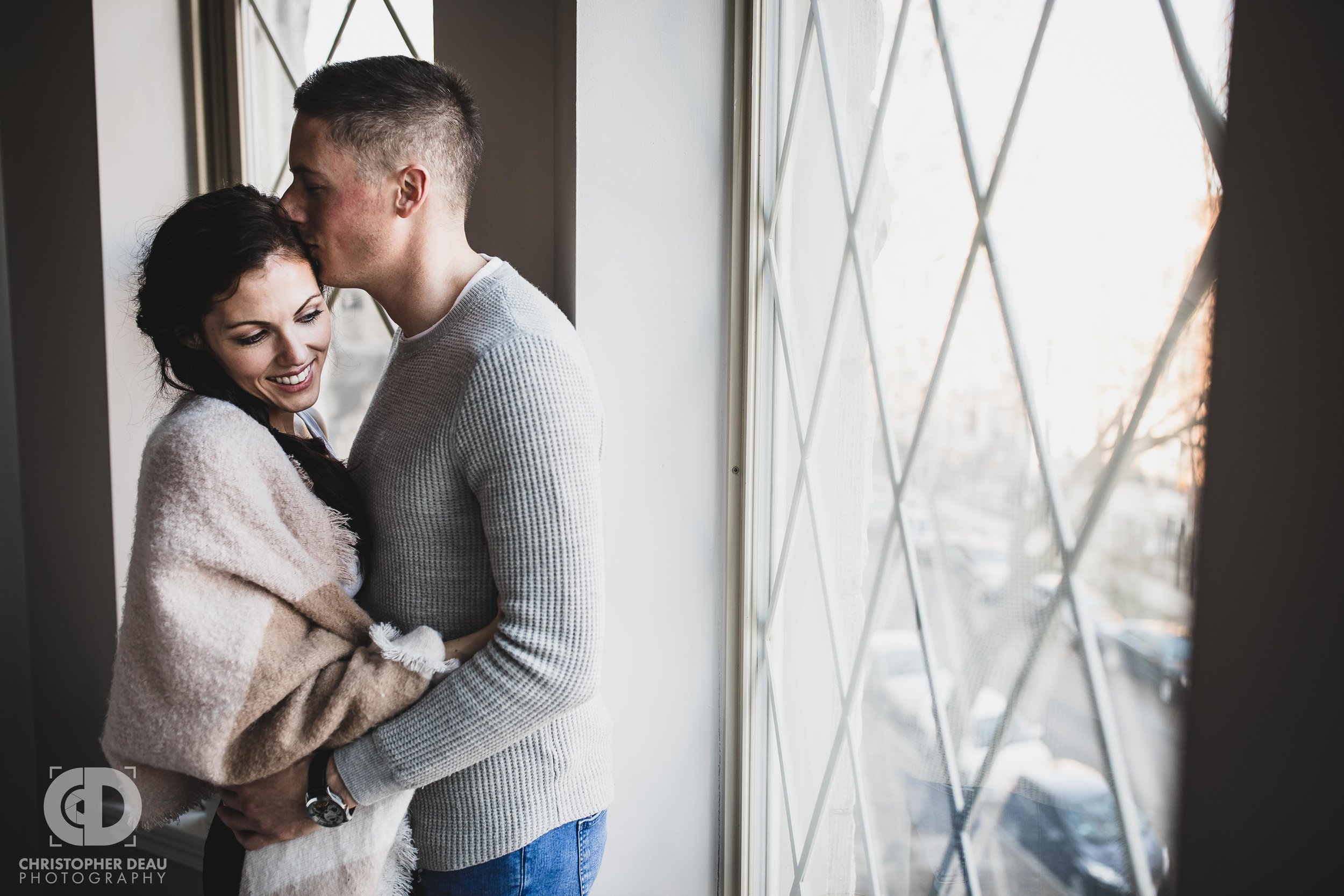 Man kissing woman during in home engagement session