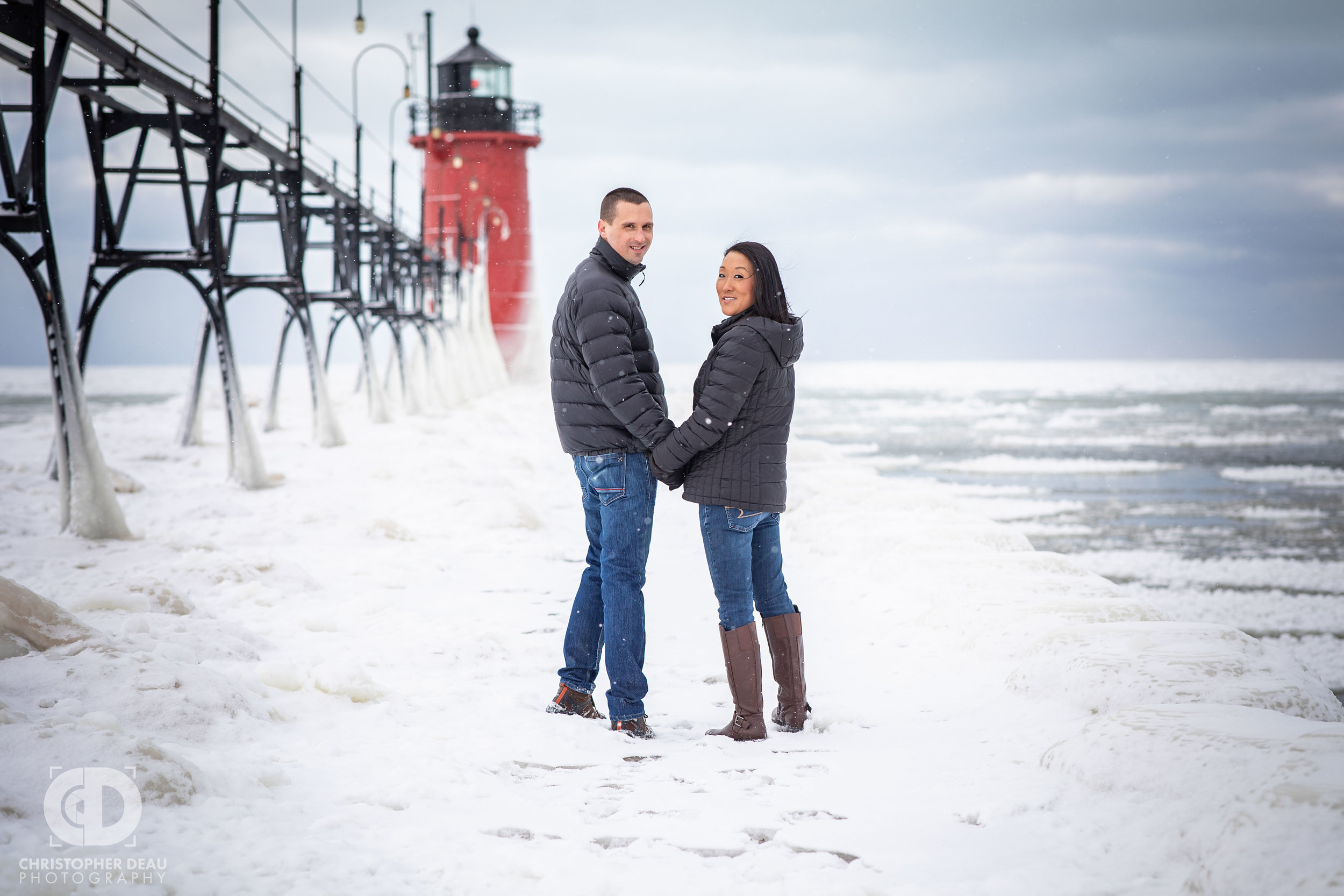 couple holding hands walking down south haven lighthouse pier during engagement session