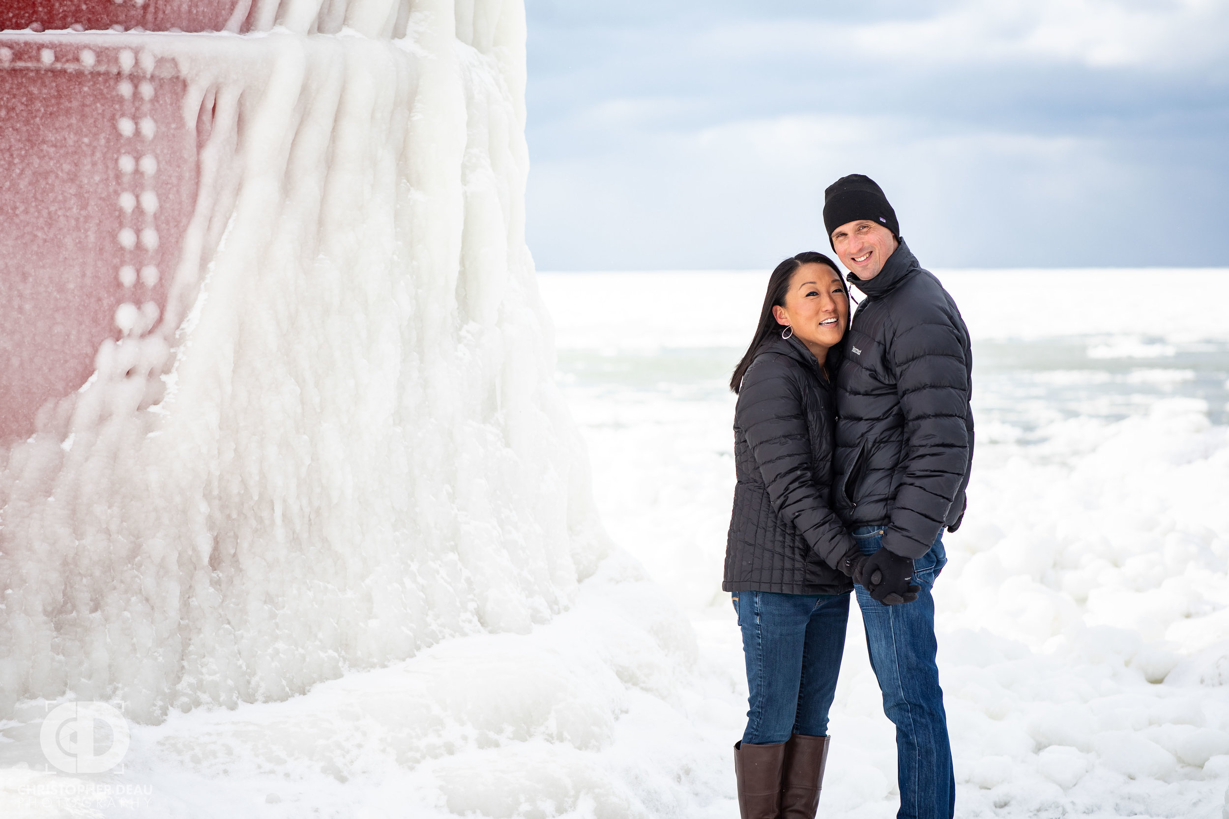 couple posing for engagement photos near a frozen lighthouse on the South Haven Pier