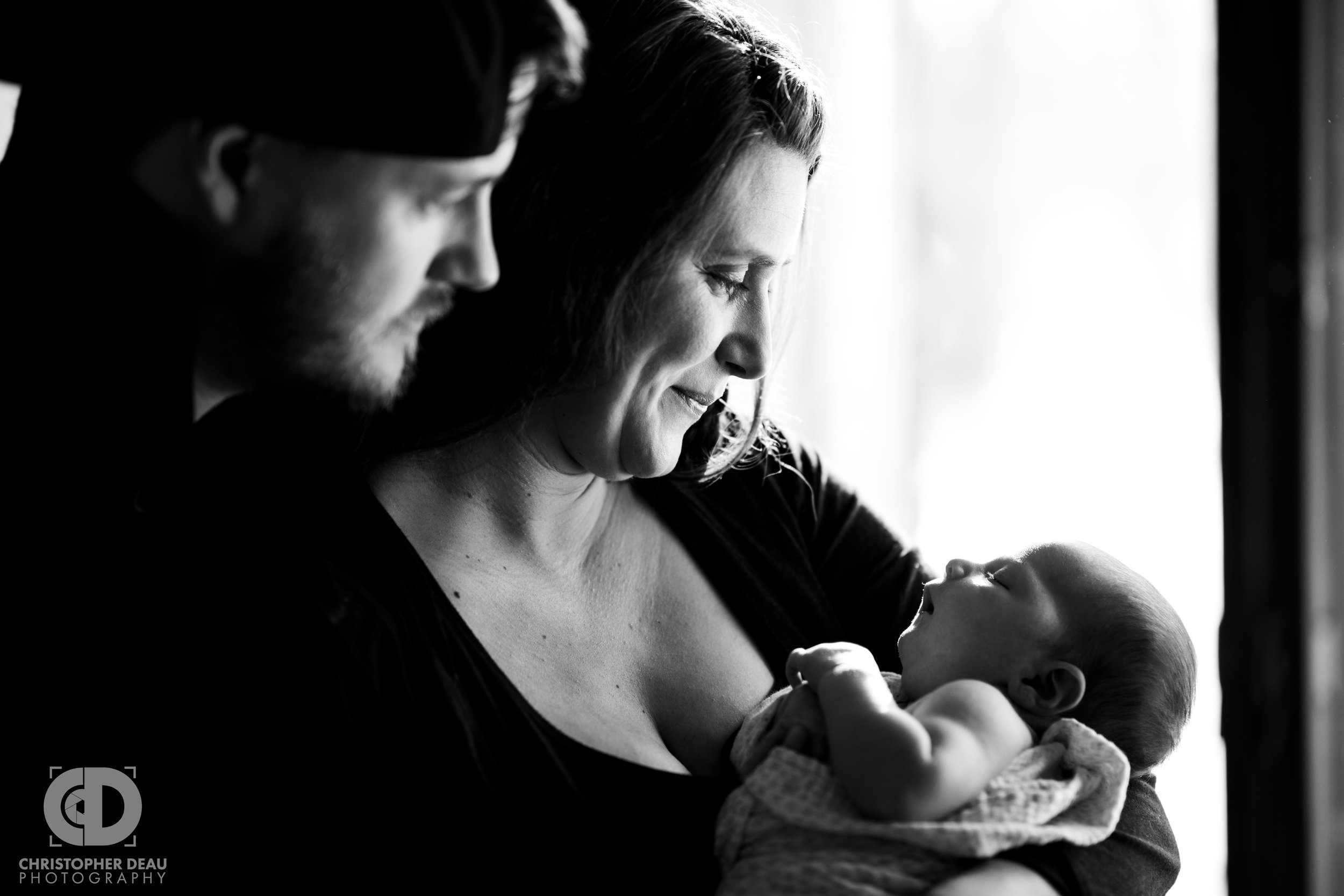 mother and father with newborn daughter black and white