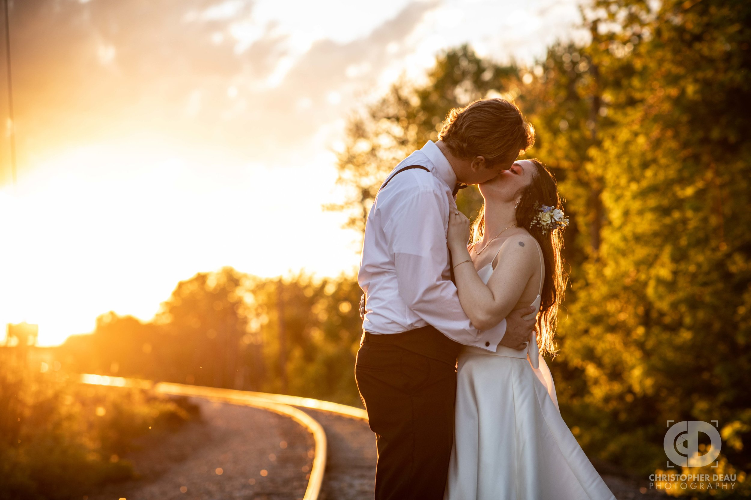 bride and groom kissing during golden hour sunset