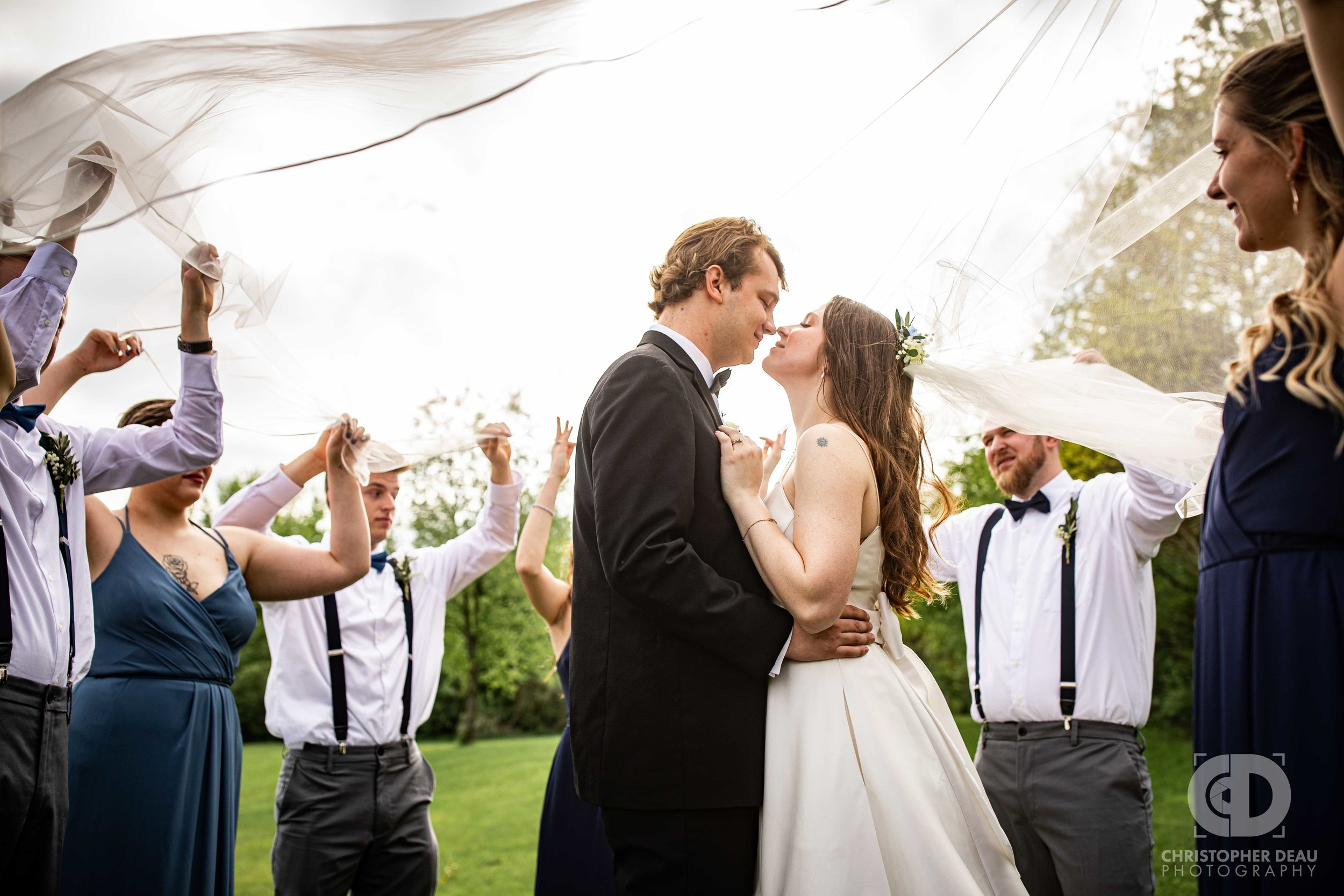 wedding party holds veil up around bride and groom