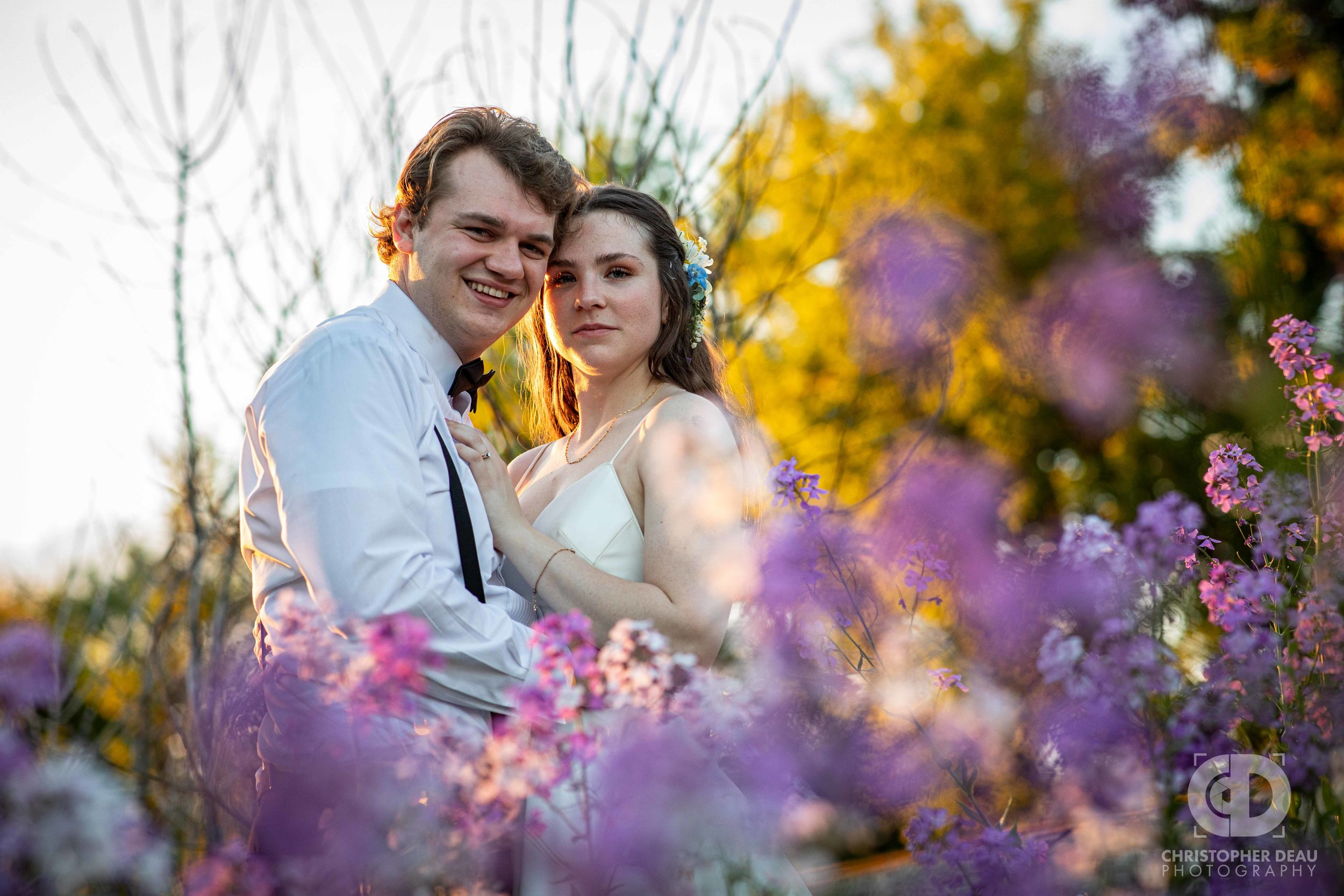 purple and white wild flowers surround bride and groom