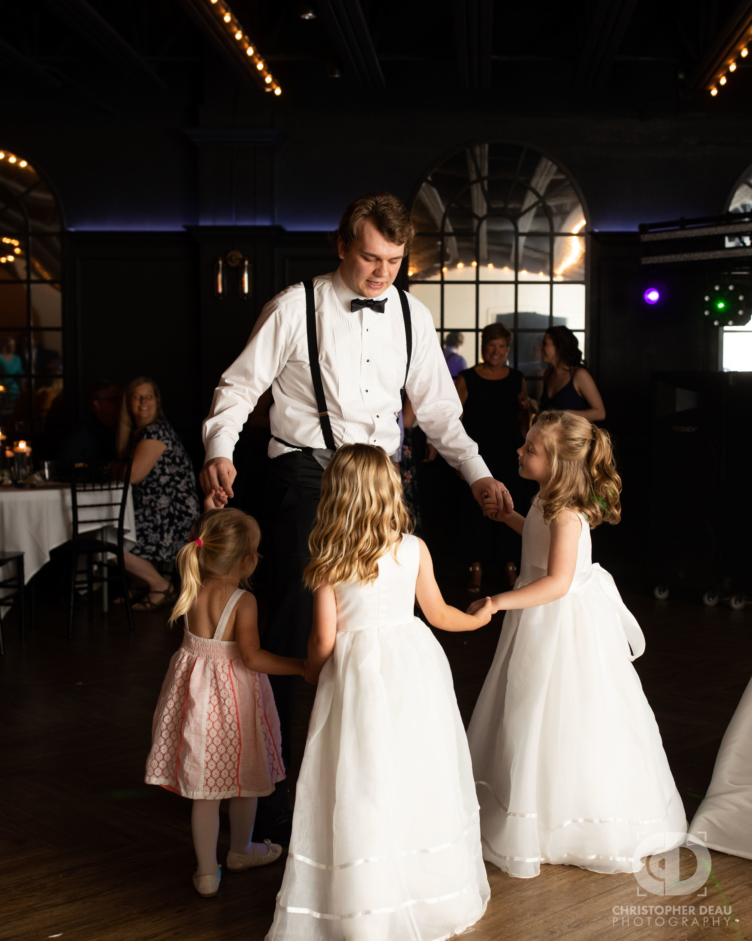 groom dances with flower girls
