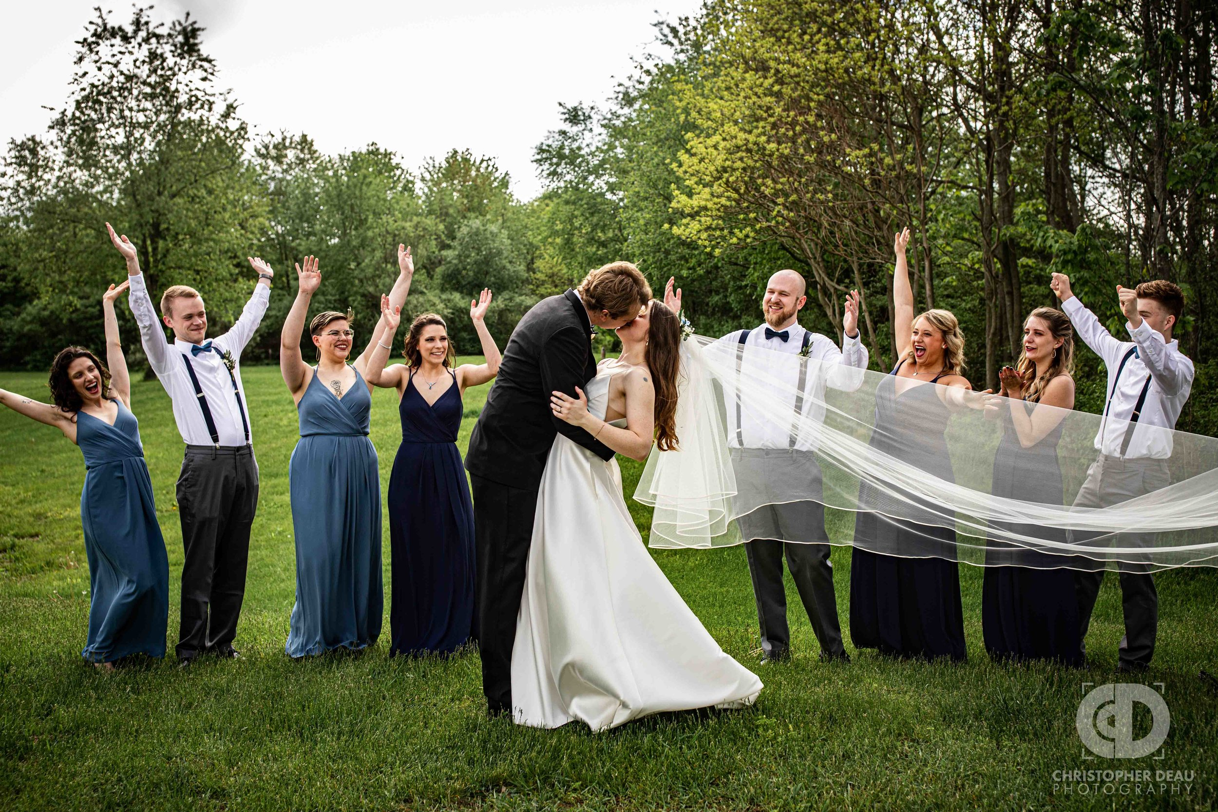 wedding party cheers as bride and groom kiss with long flowing veil