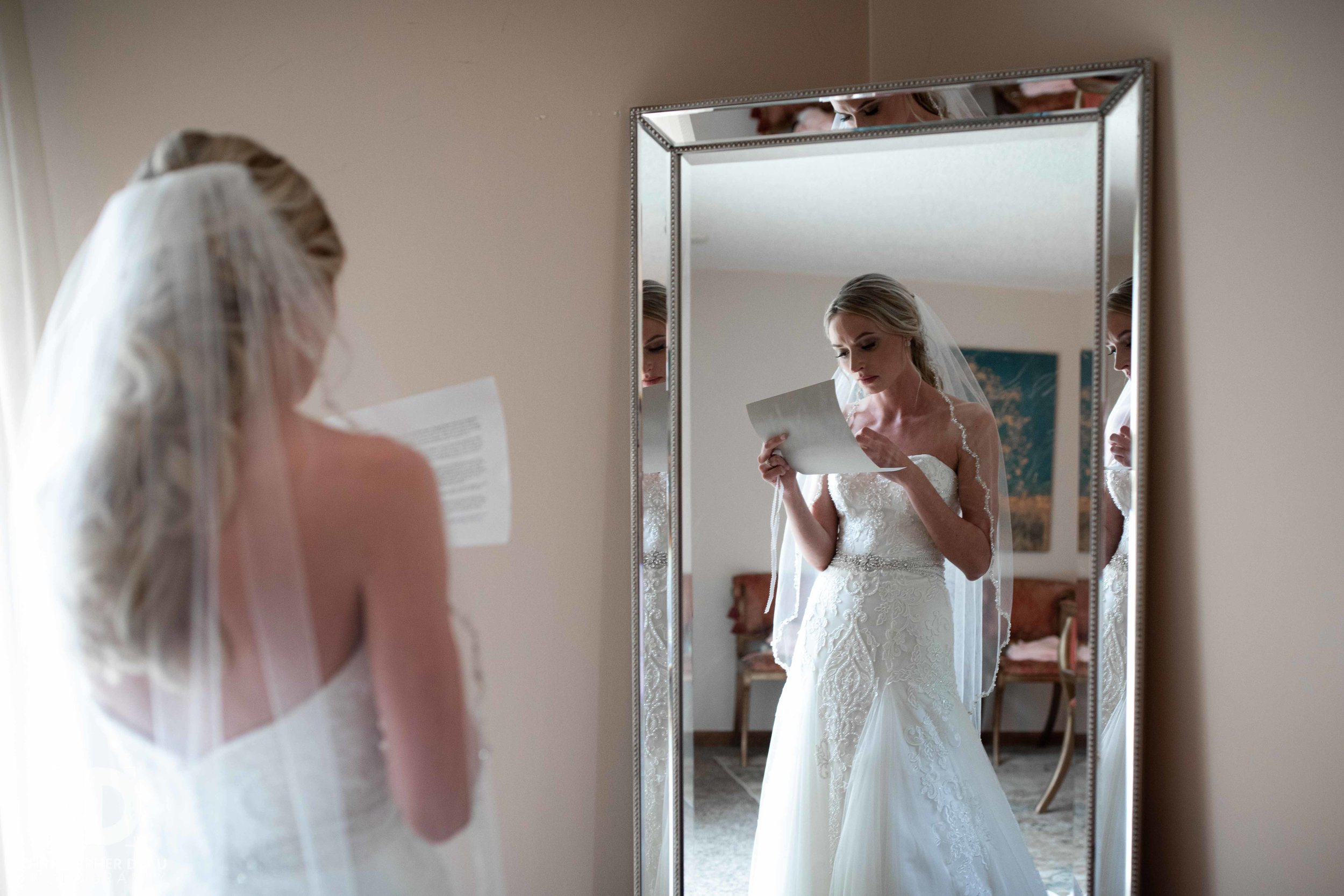 bride reading letter from the groom in front of a mirror