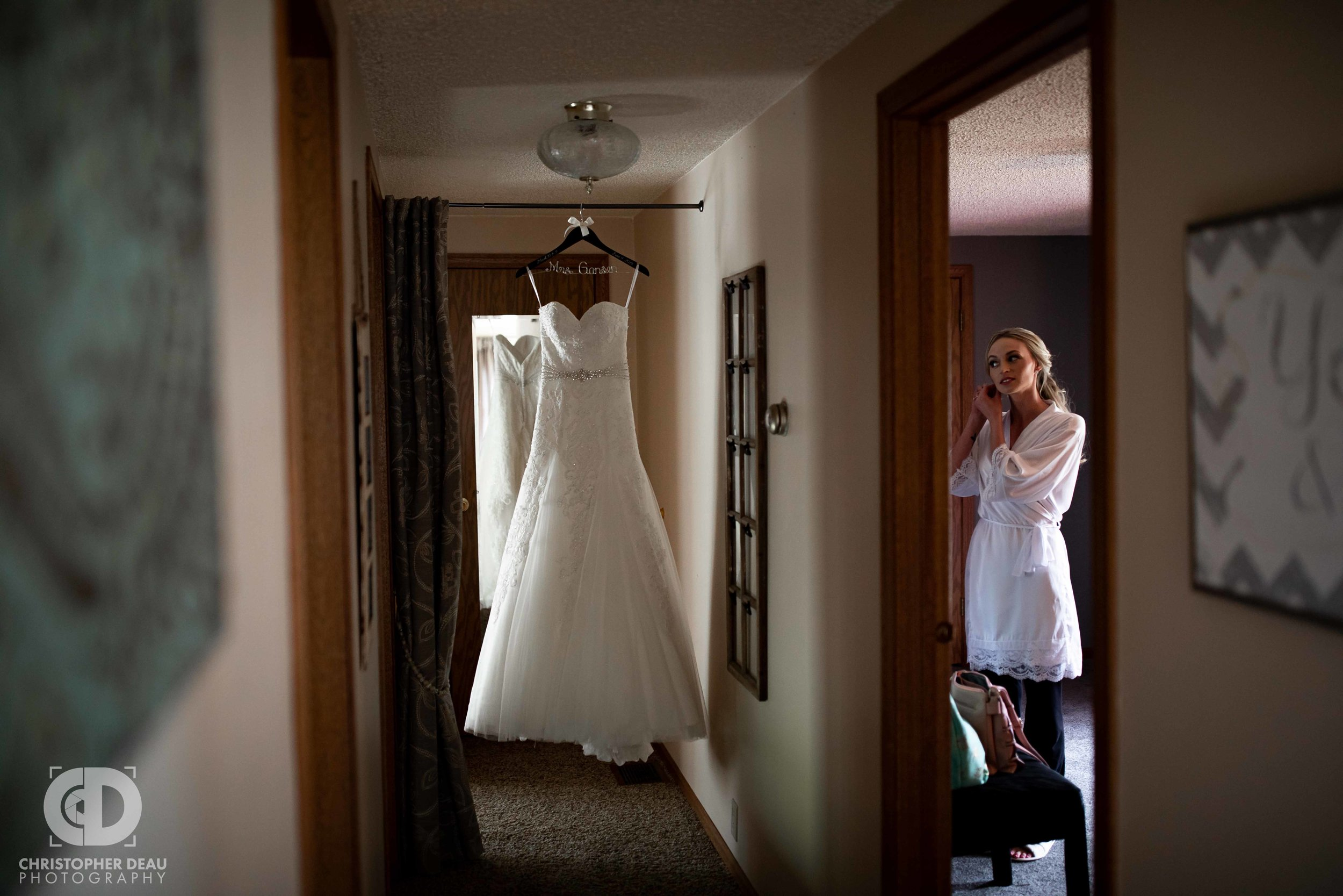 the brides wedding dress hanging in a hall