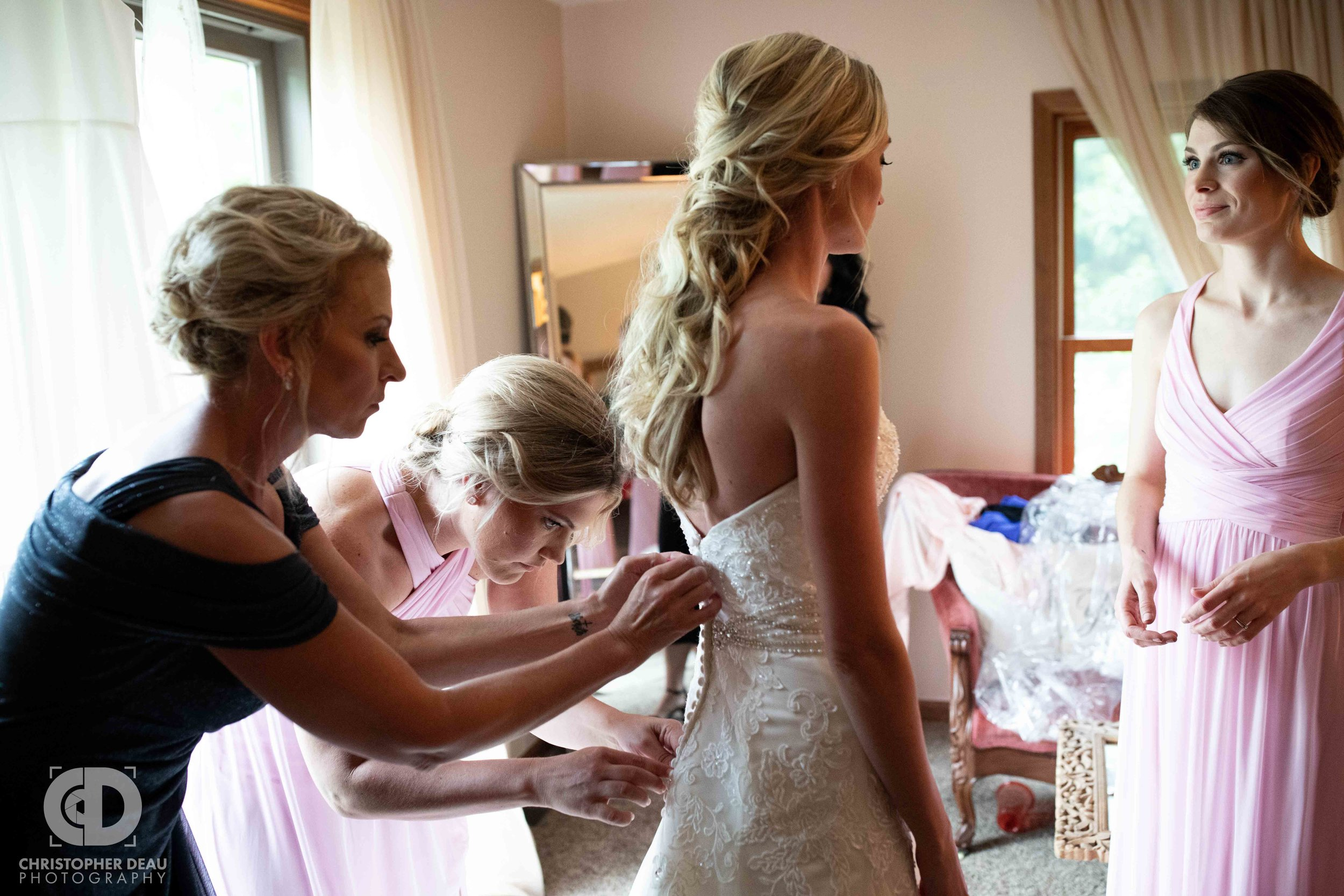 bride getting her gown zipped up