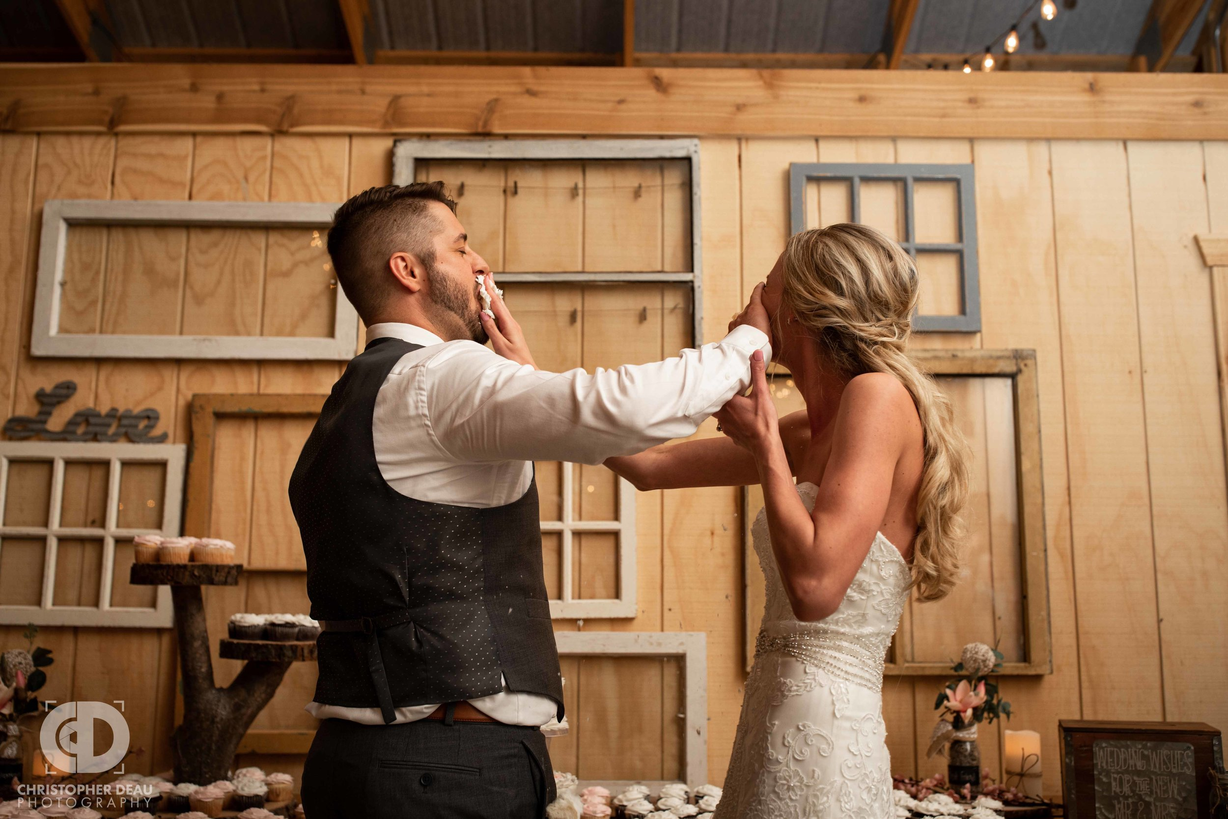 bride and groom smashing cake in faces