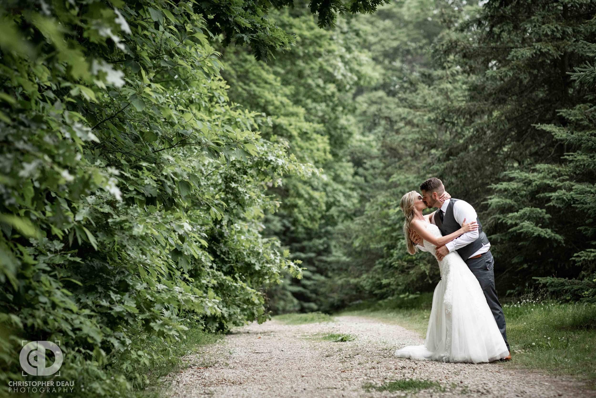 bride and groom on a dirt road with pine trees at Gable Hill