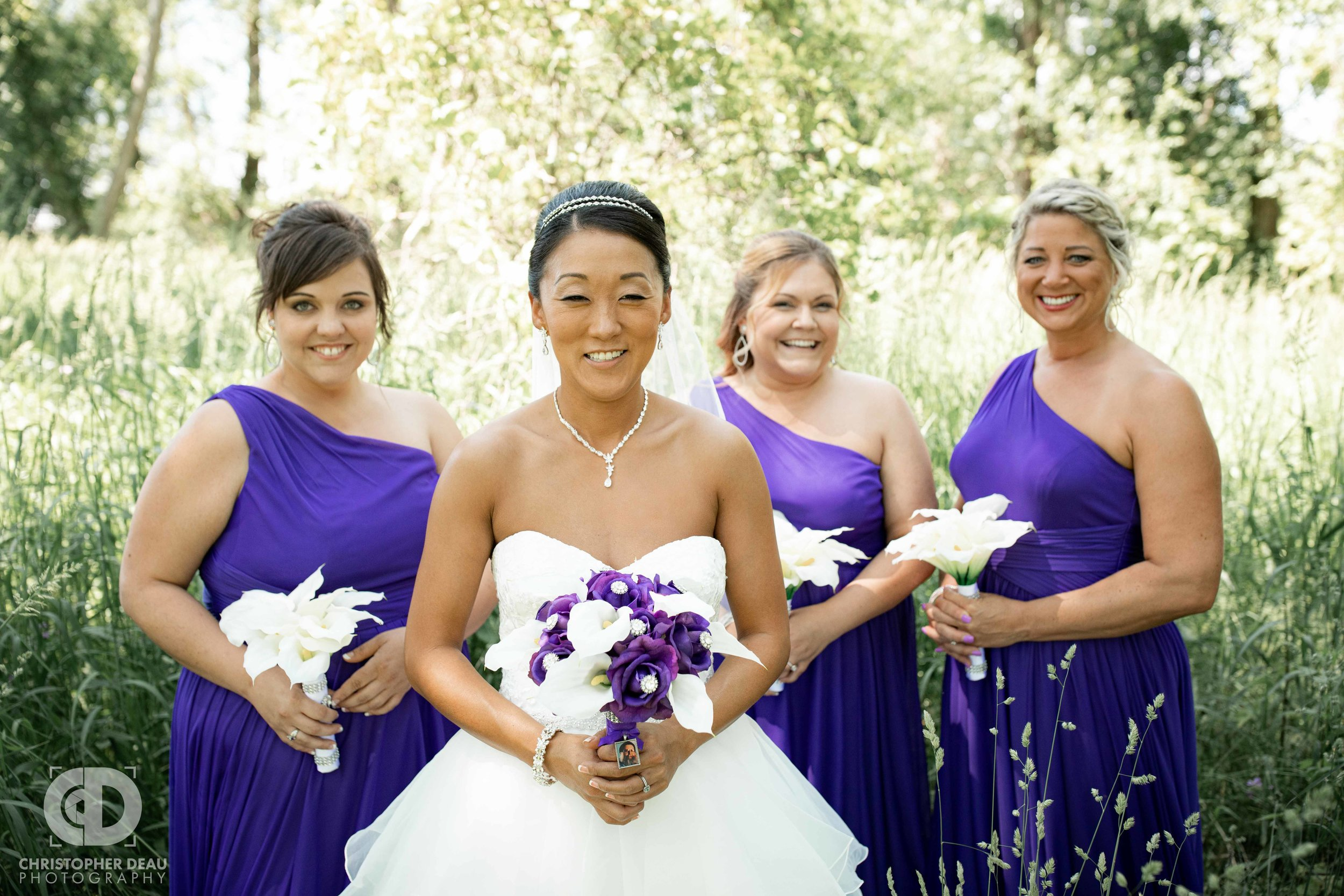 Bridesmaids with bride in tall grass