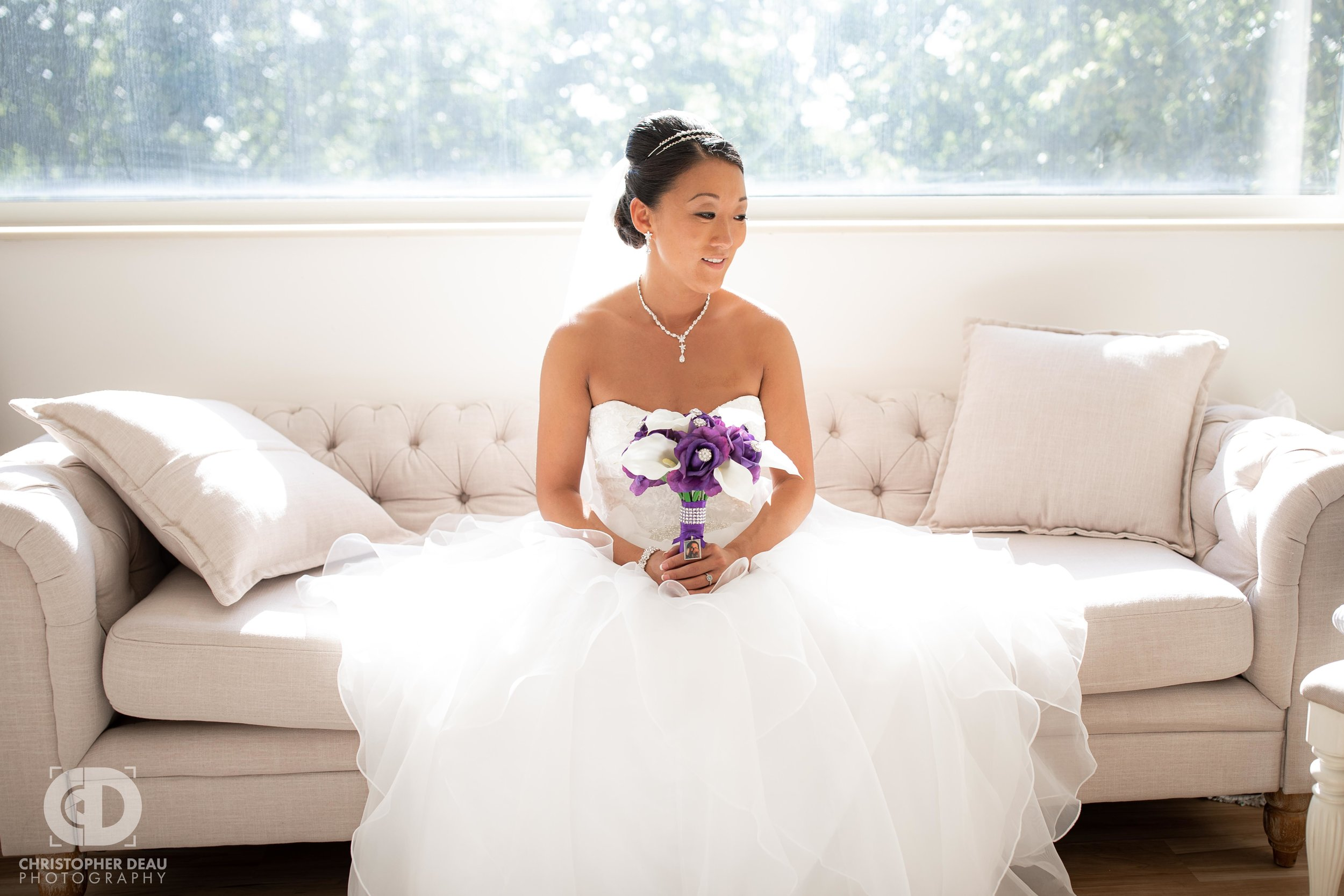 Bride with bouquet on a couch at the WMU Fetzer Center bridal suite