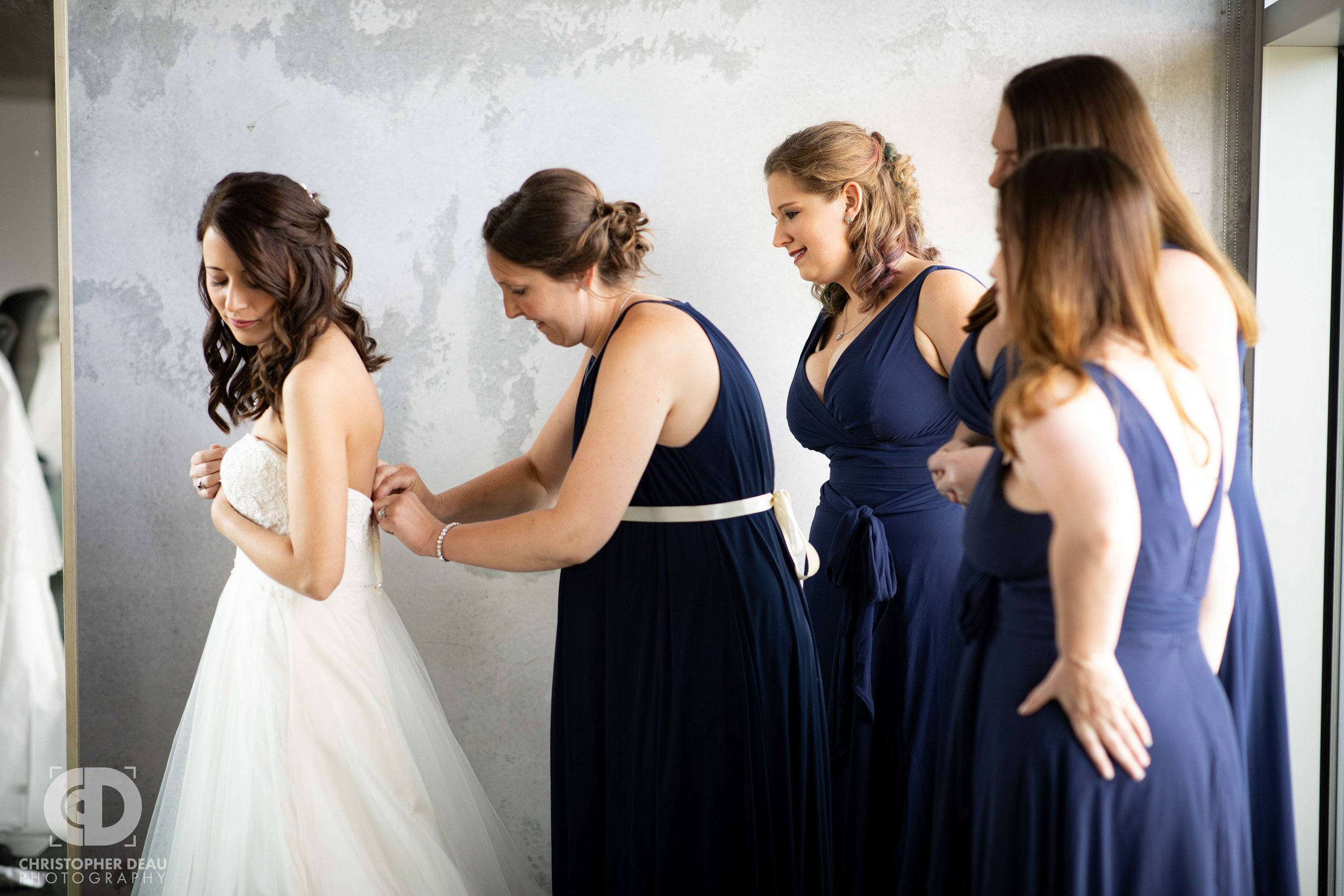 bridal party getting the bride into her dress