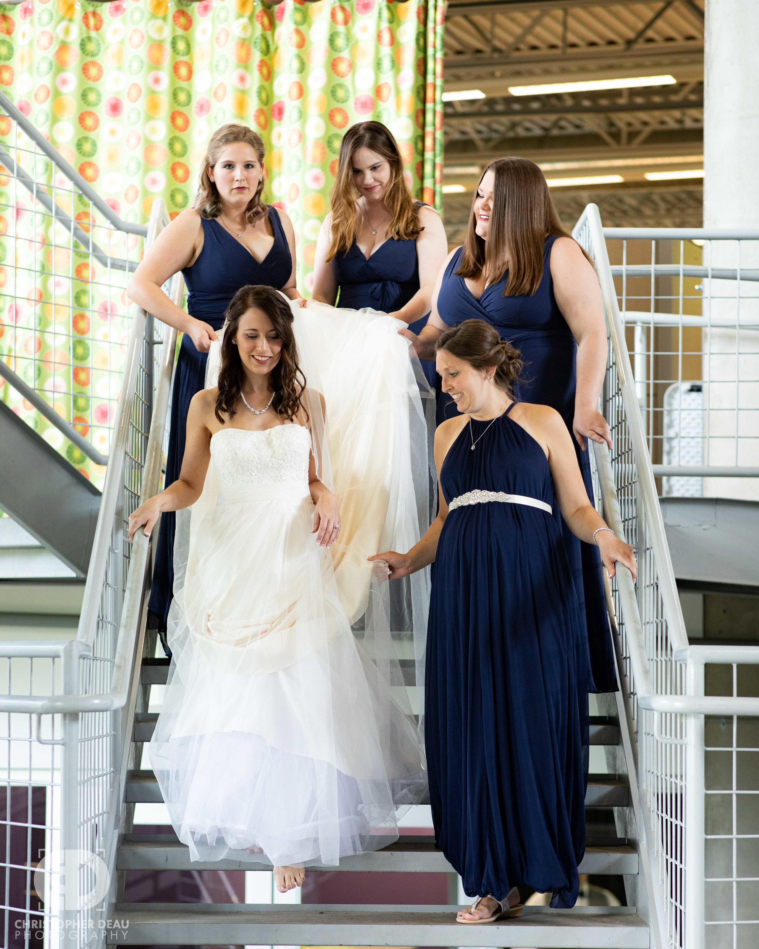 bridesmaids helping bride down the stairs