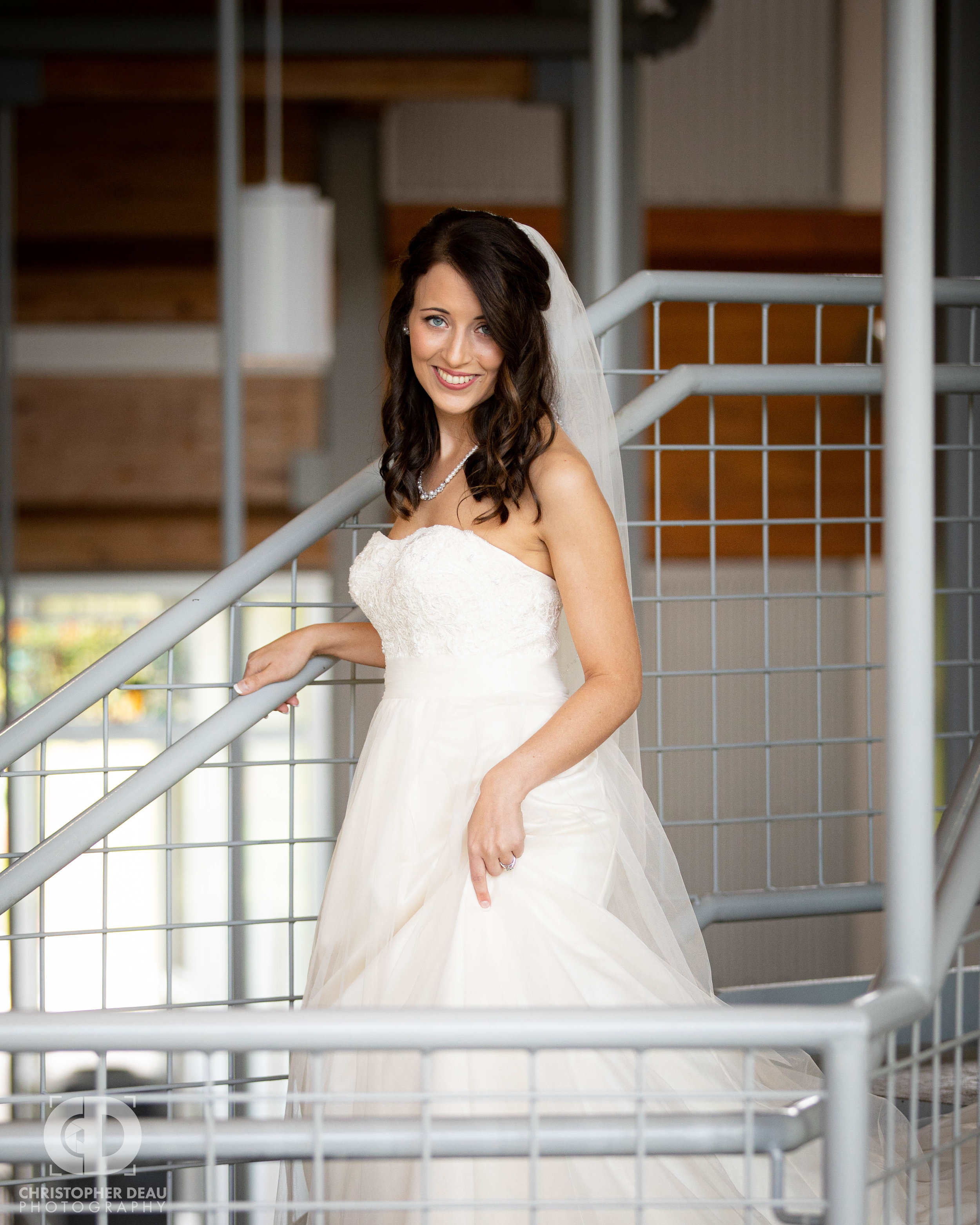 portrait of bride in her white dress in industrial building